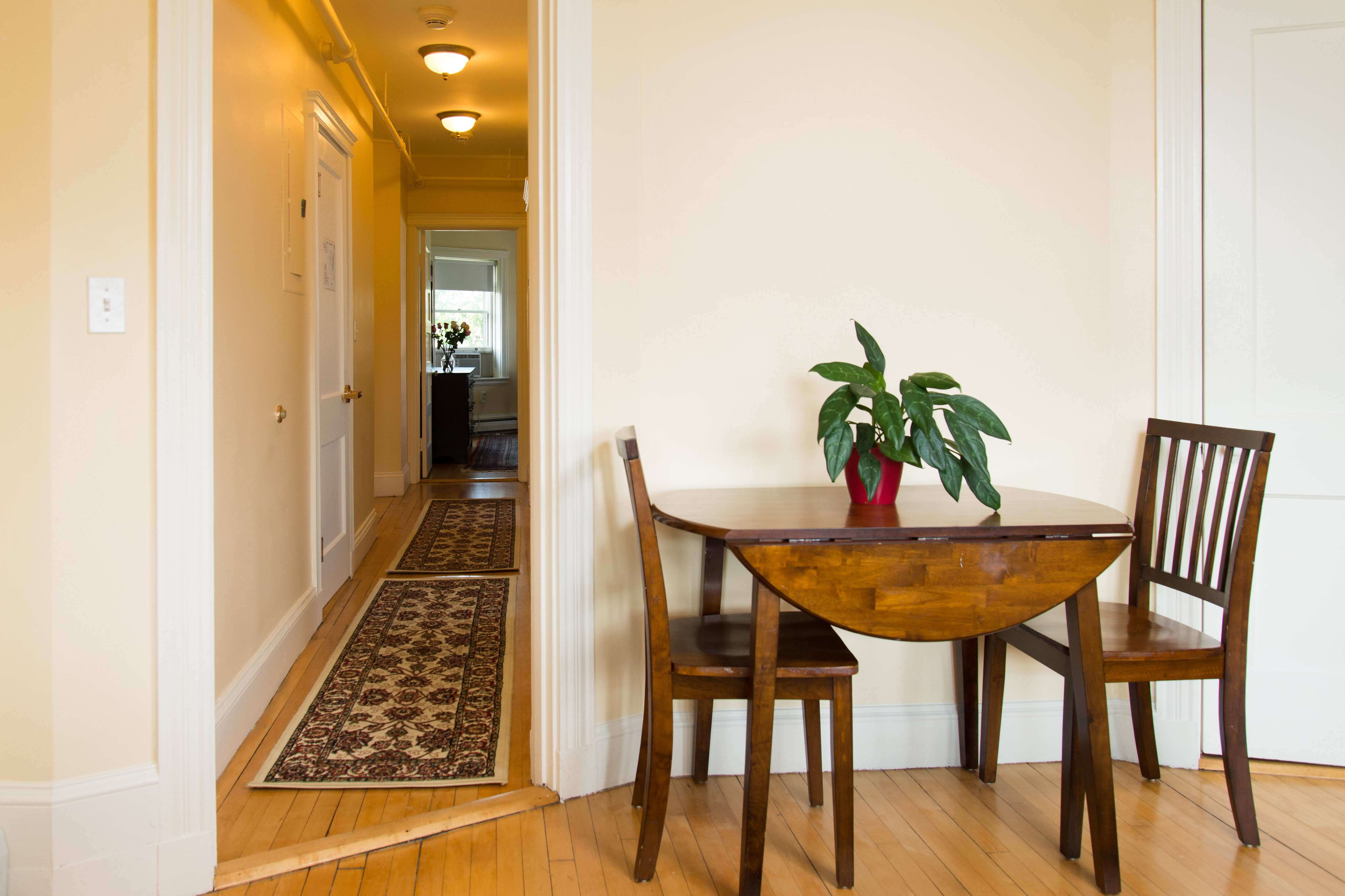 Dining table leading to hall space in 83 Brattle Street one bedroom with hallway apartment
