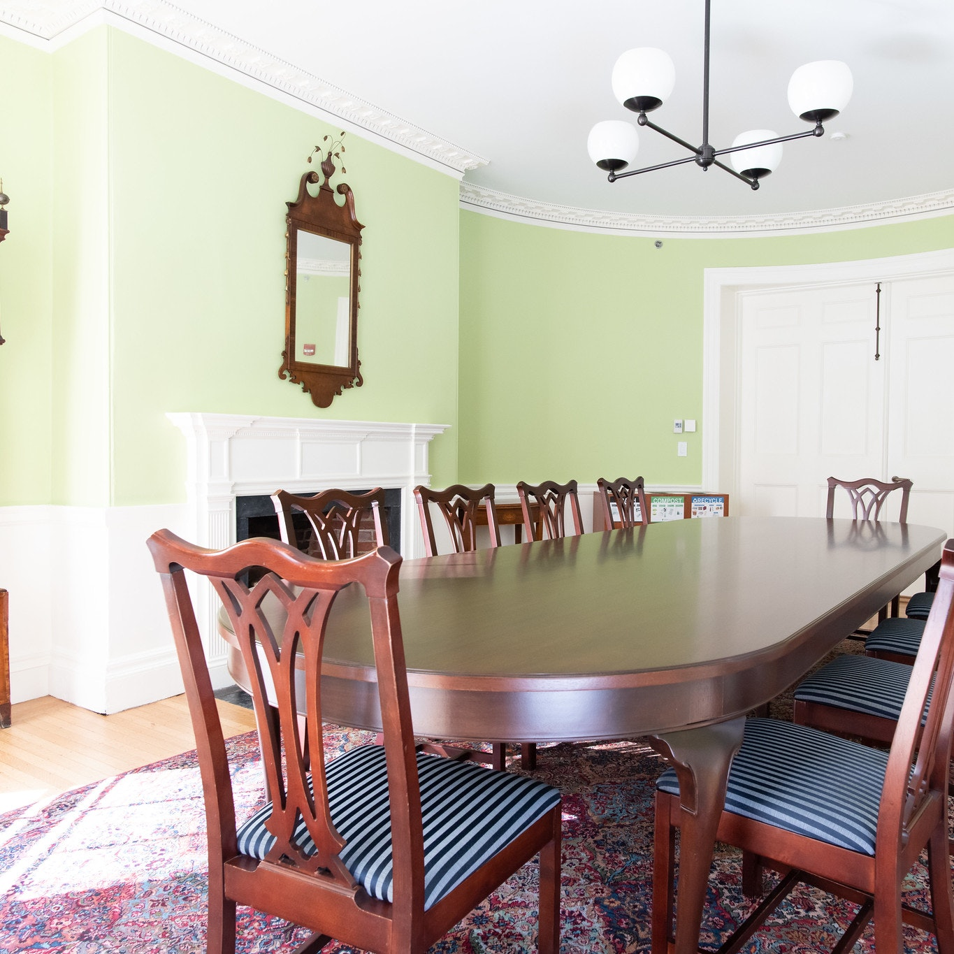 Another angle of the Gardiner Room, Conference table with 10 seats lined around table. Grandfather clock in the left corner of room. White, double door entrance on the other end of the conference table.
