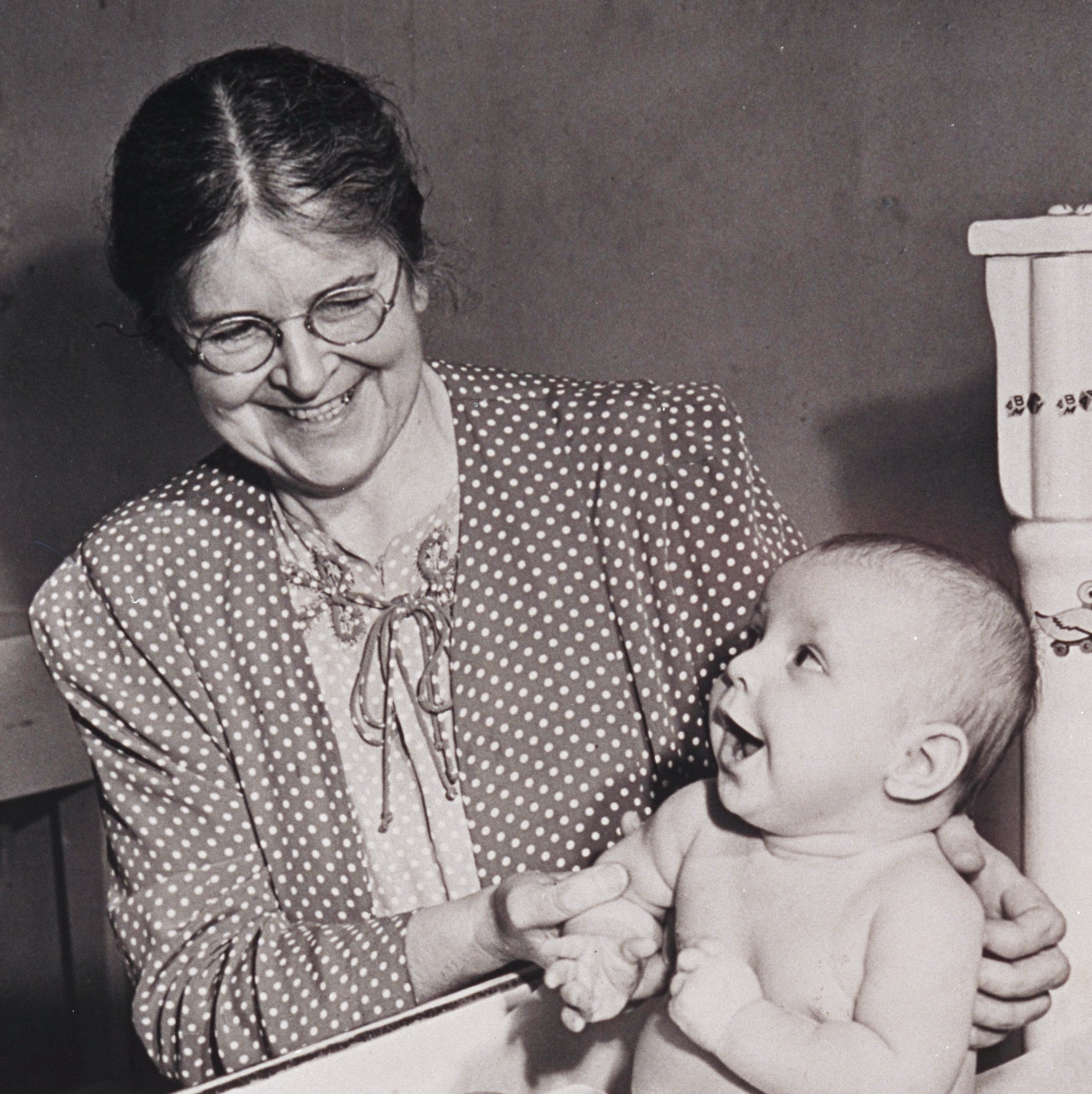 Martha May Eliot holding a child