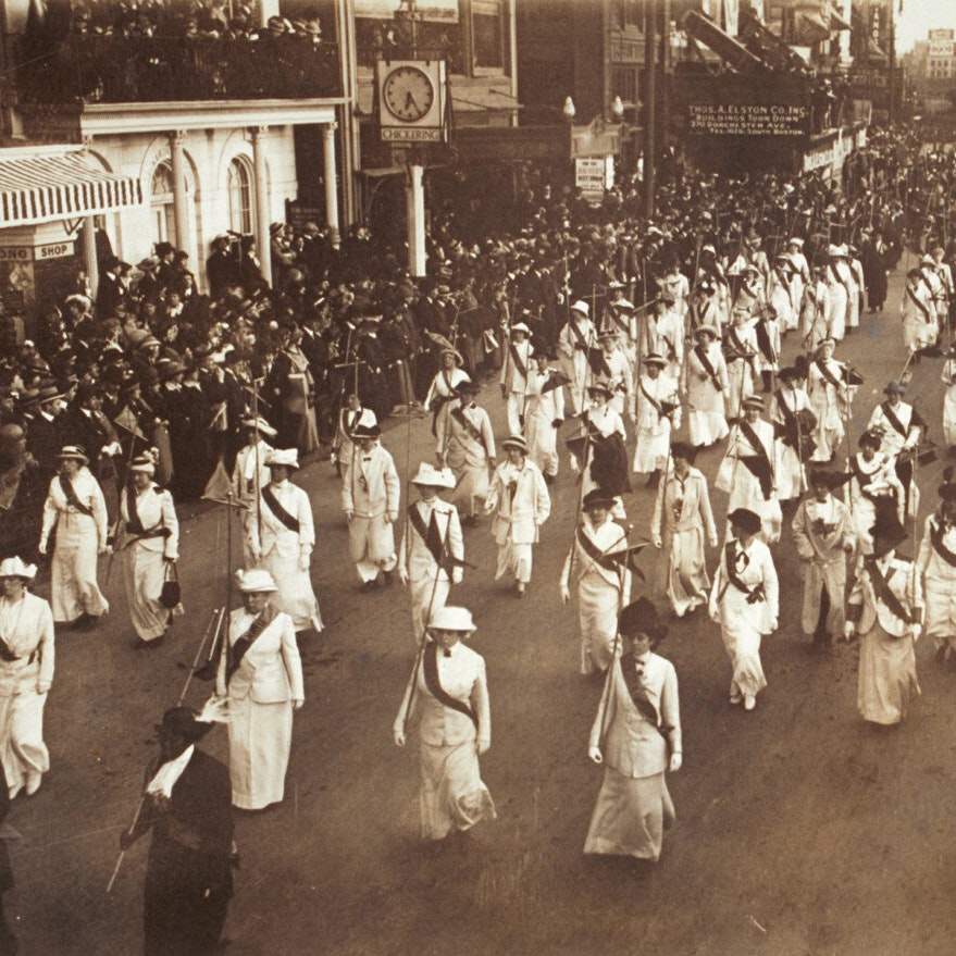 Sepia toned image of a regiment of women in uniform (white or pale clothes and a dark sash) carrying staffs and marching in formation in a suffrage parade