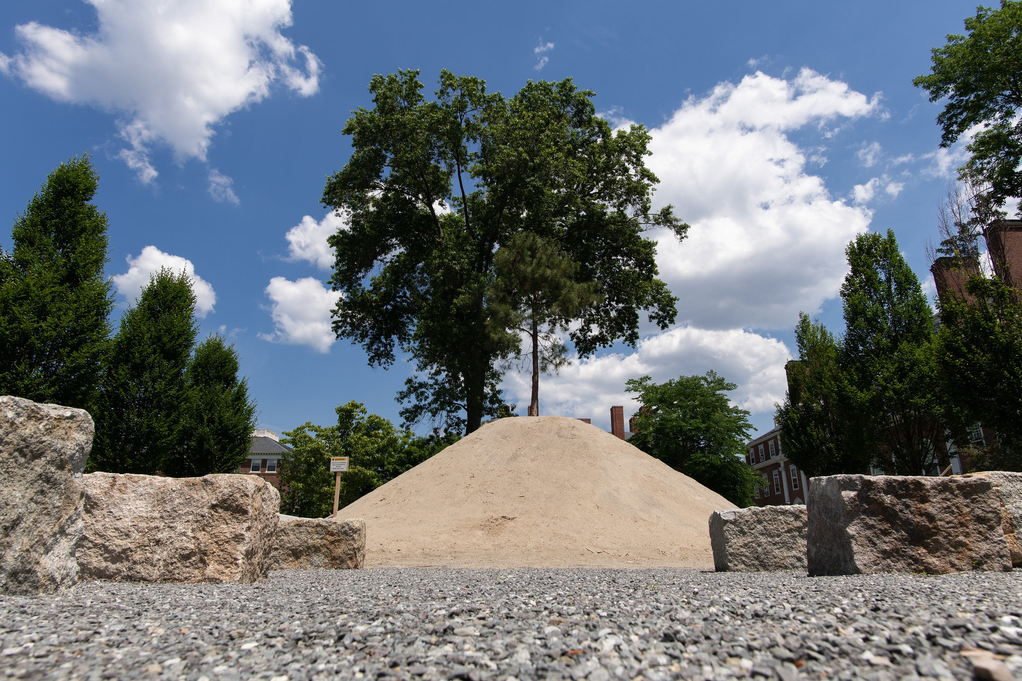 A mound of sand is planted with rows of granite benches
