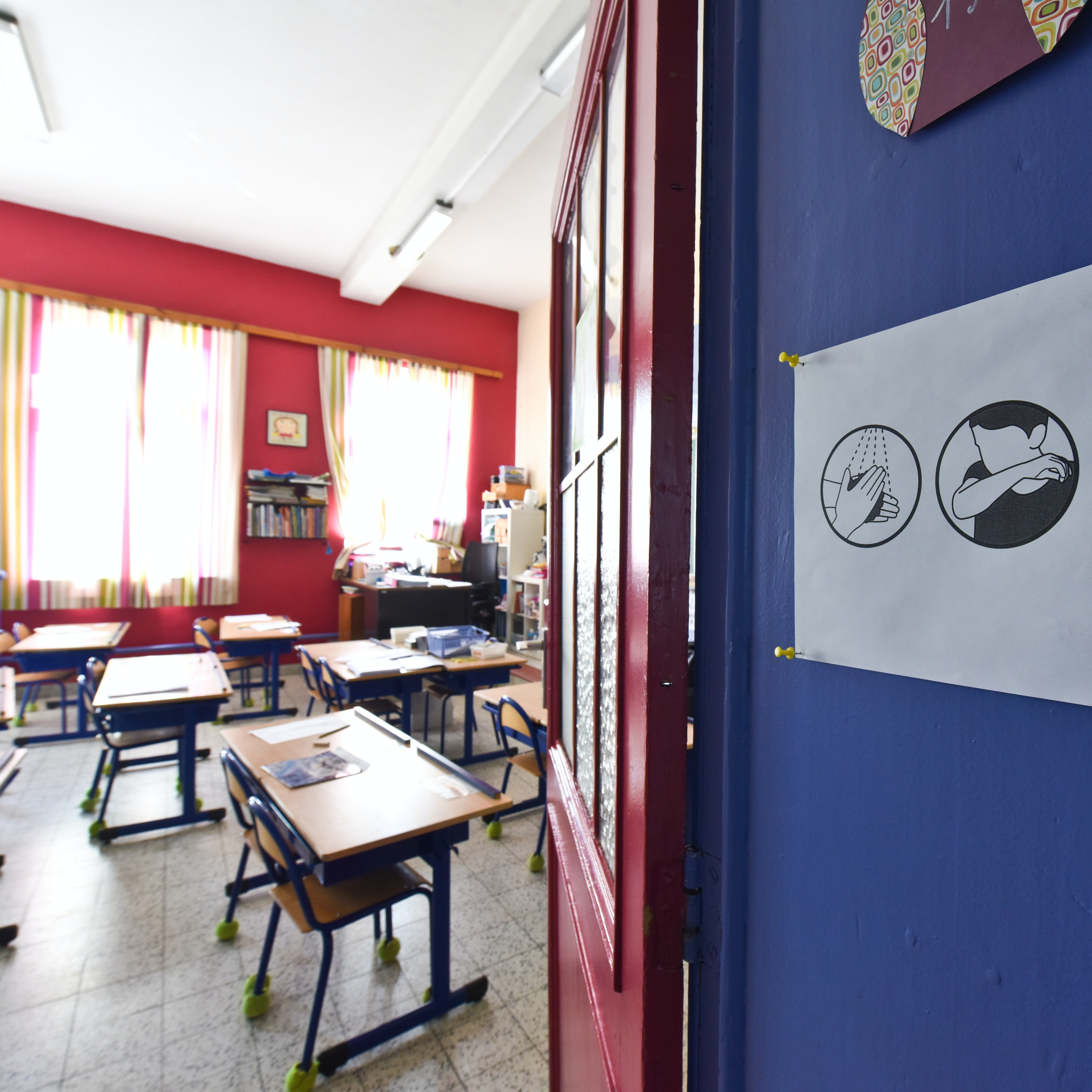 An empty classroom. A sign with instructions on preventing the spread of viruses is posted on the door.