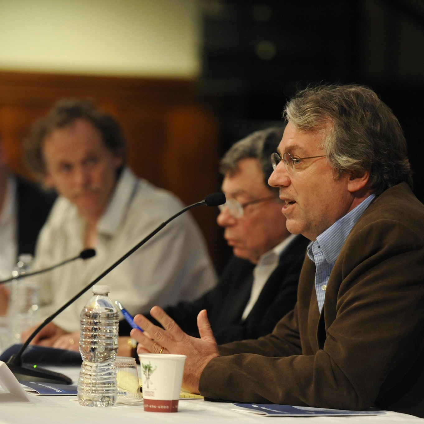 Four men sit at a panel table. One is speaking into a table microphone while the others listen.