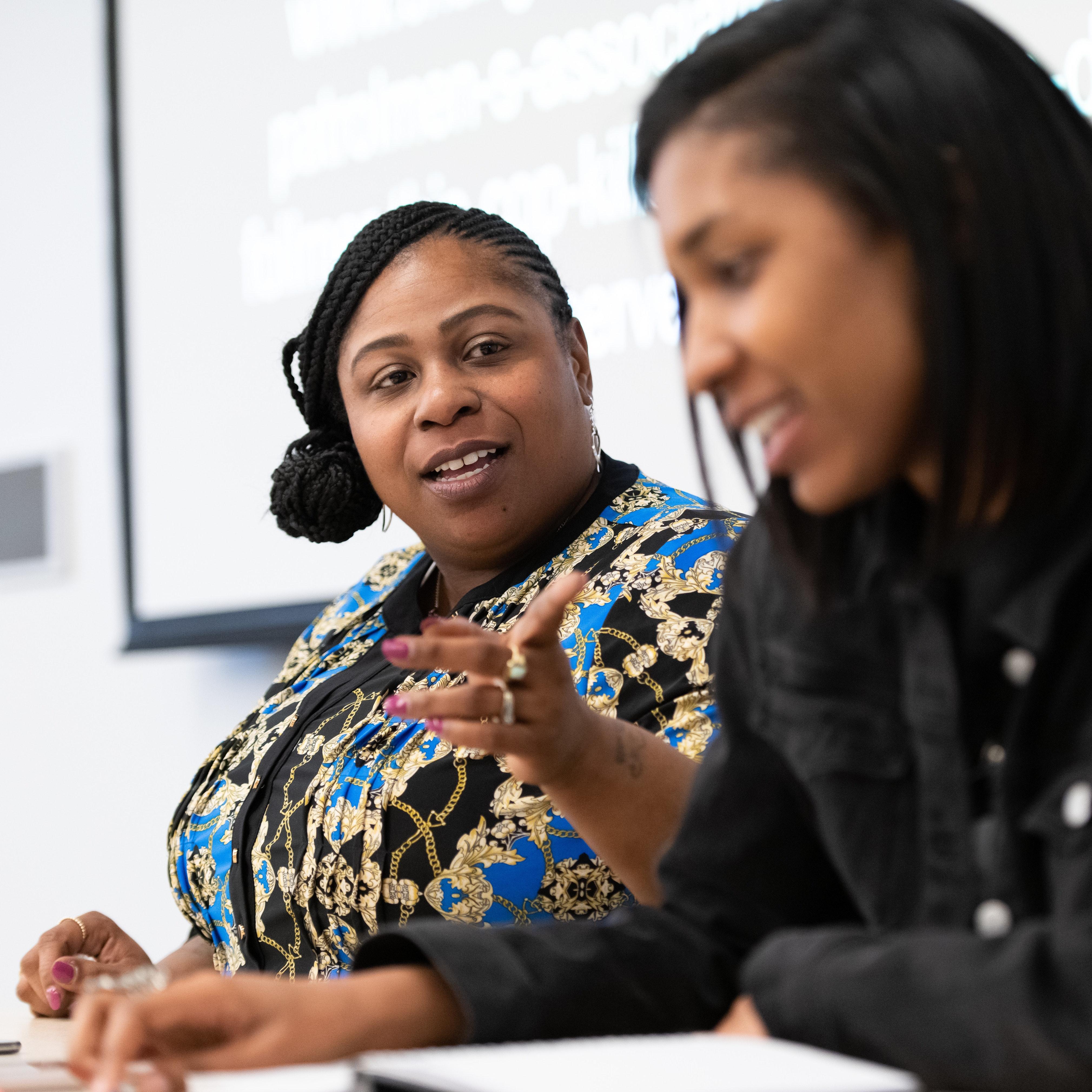 Two women speak on a panel.