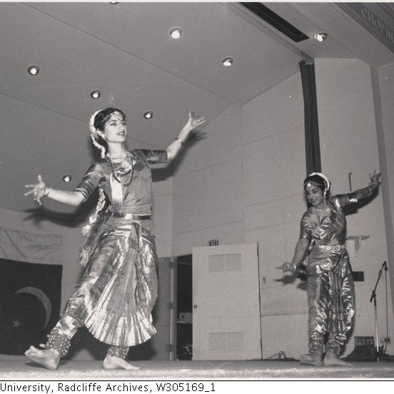 Two women on stage performing Bharatanatyam dance