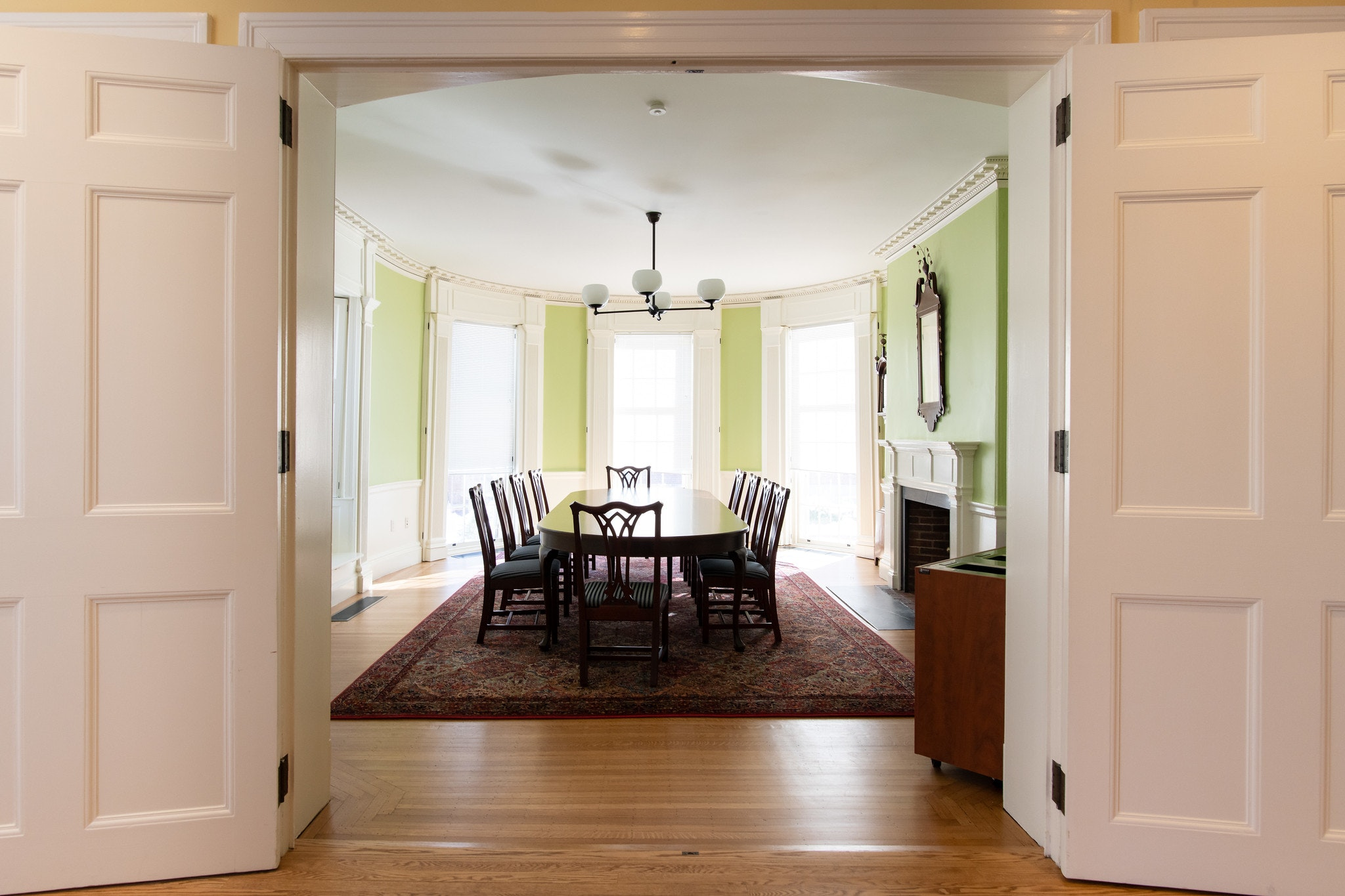 View from entrance with two white double doors. Conference table with 10 seats lined around table.