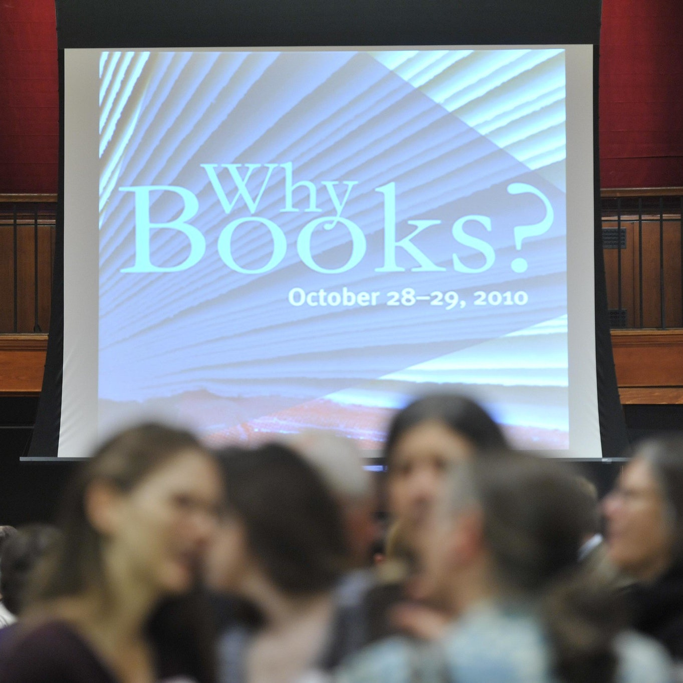 "An audience gathers in front of a screen that says ""Why Books?""—the title of the event."