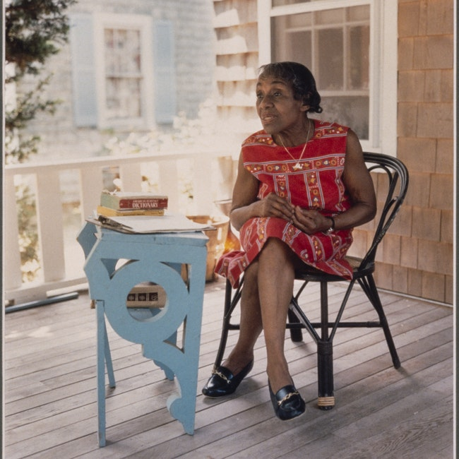 Portrait of Dorothy West, seated in chair on a deck