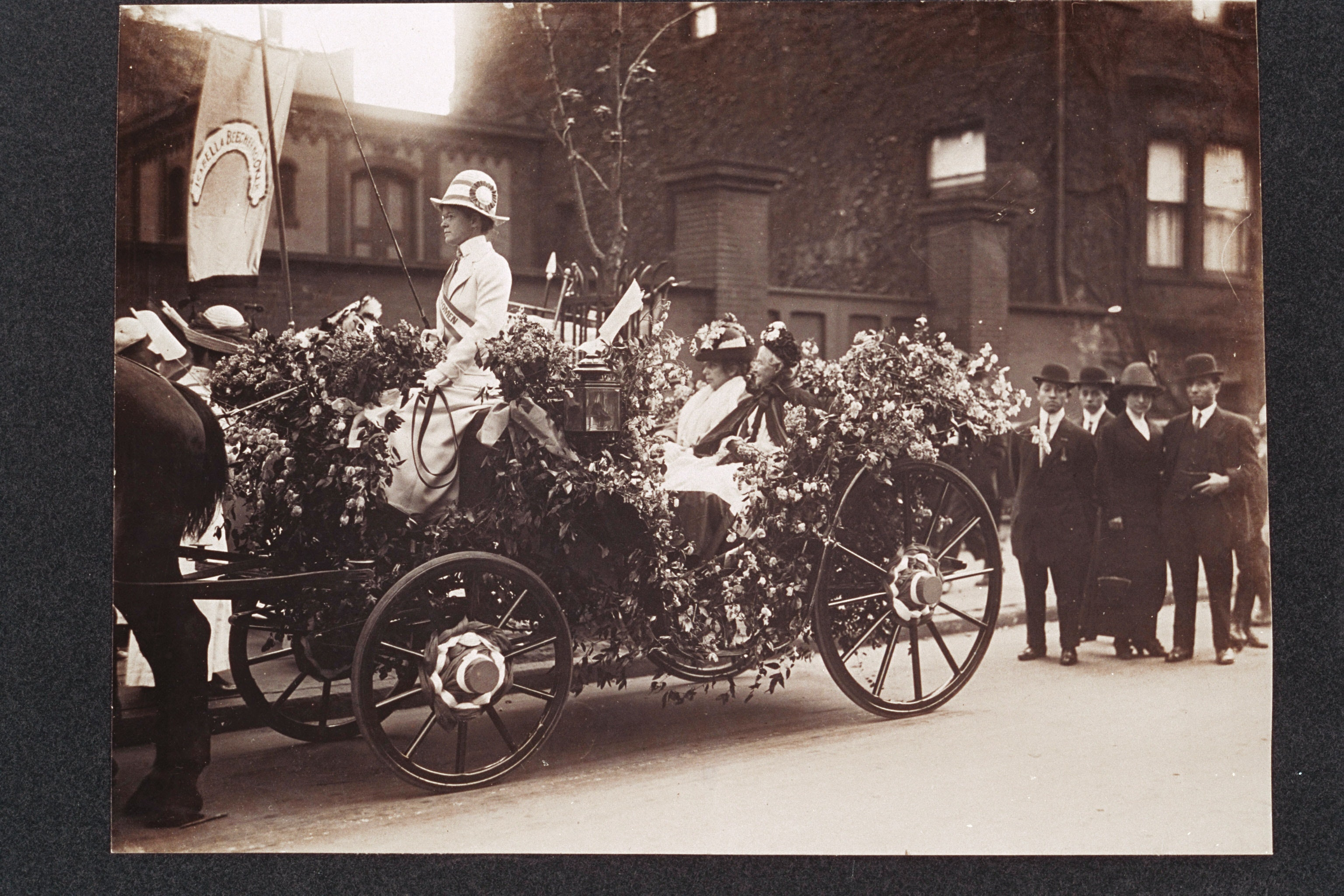 View of Antoinette Louisa Brown Blackwell (right) and Alice Stone Blackwell (left) seated in a horse-drawn carriage decorated with flowers for a parade