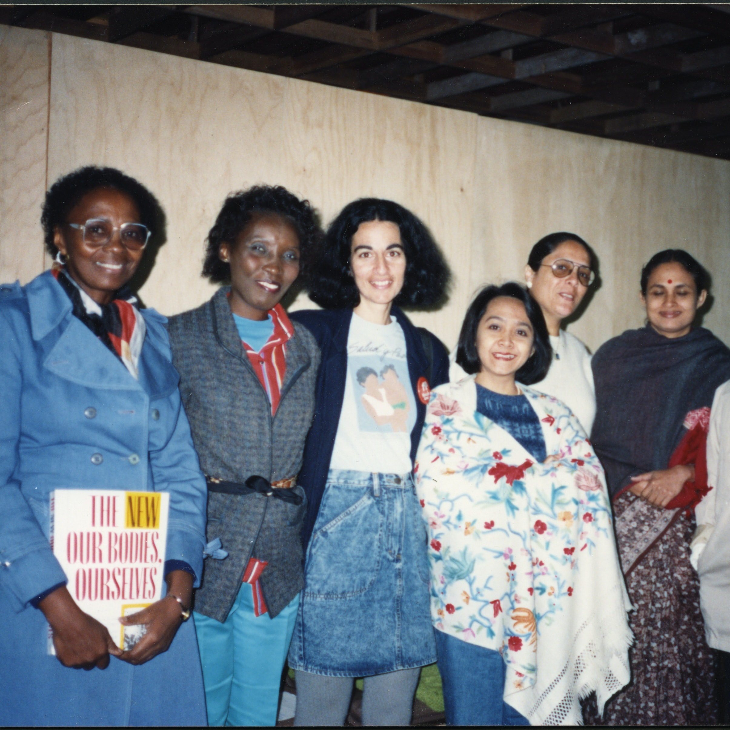 Group of women at International Women's Health Coalition (IWHC)/World Health Organization meeting, holding a copy of The New Our Bodies, Ourselves