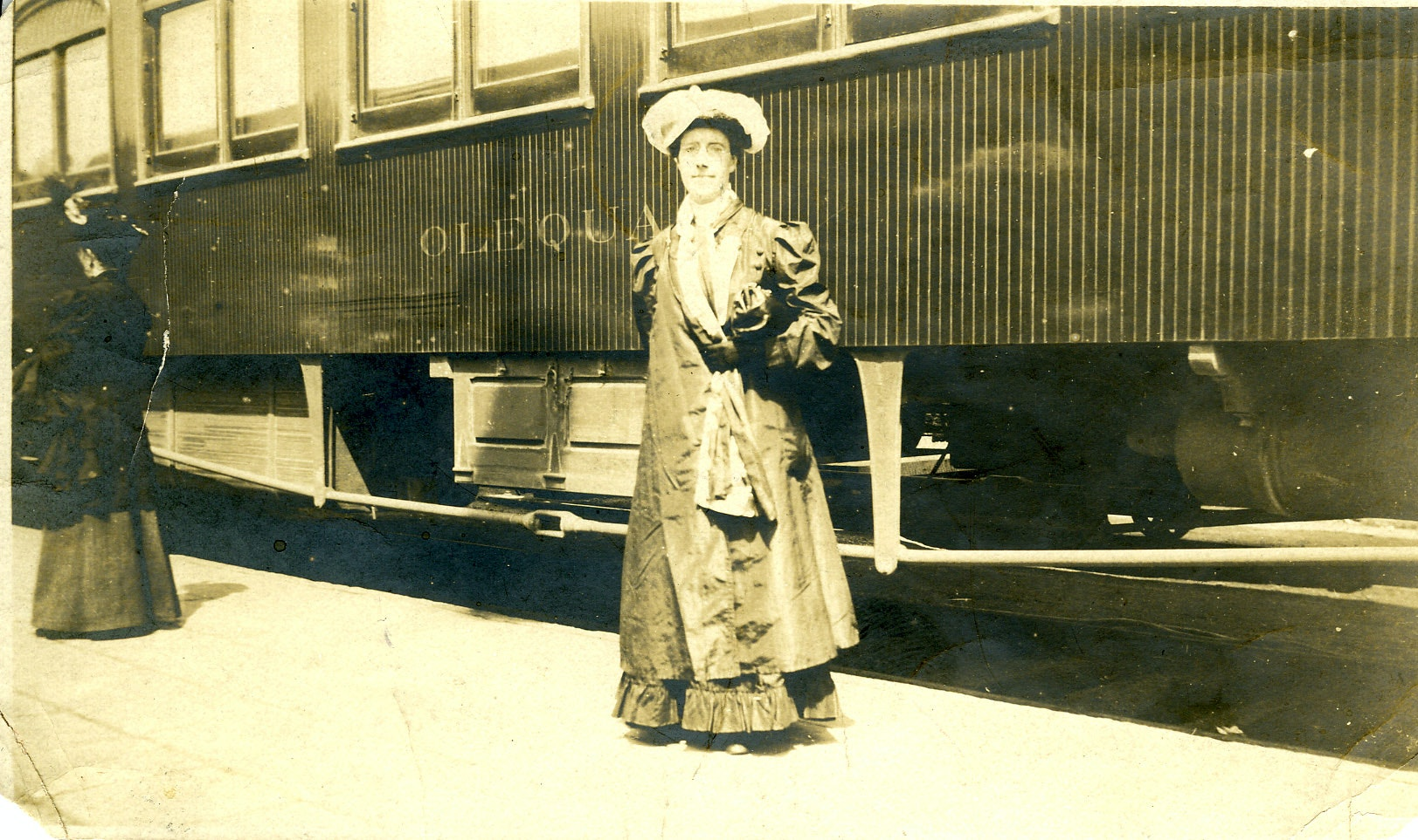 Portrait of Charlotte Perkins Gilman, standing outdoors in front of a train