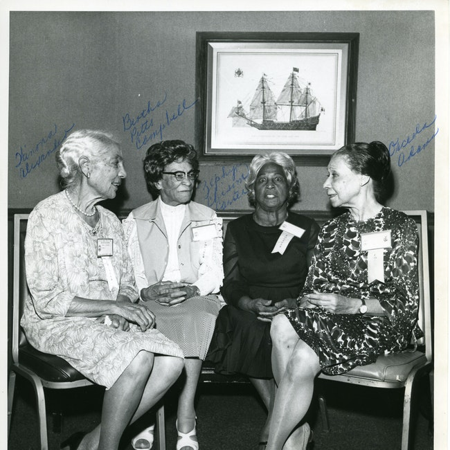 Group portrait of four Delta Sigma Theta members, Winona Alexander, Bertha Pitts Campbell, Zephyr Chisom Carter, and Orceola Adams, seated at an unknown event
