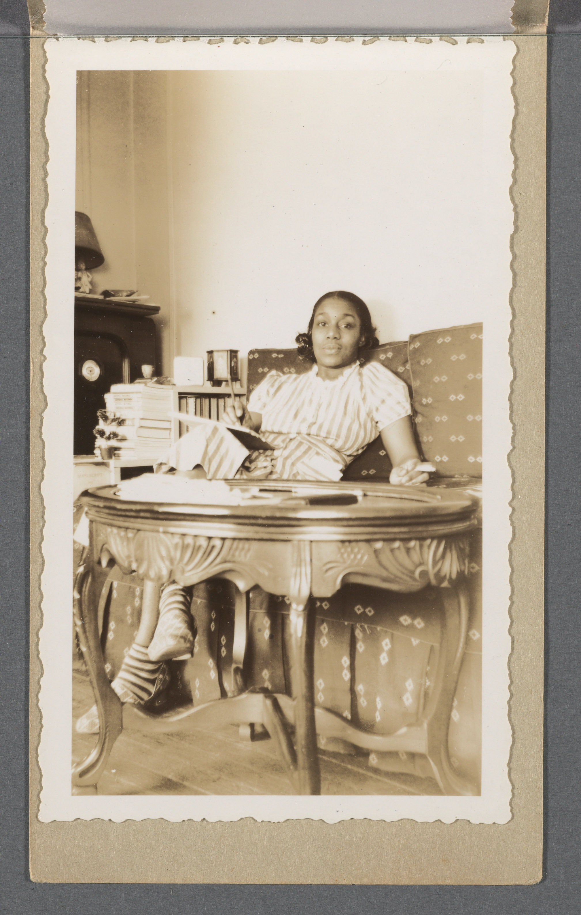 Dorothy West in her New York City apartment. West is seated on a couch, holding a pad of paper on her lap