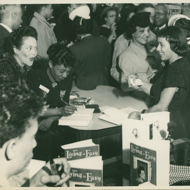Dorothy West autographs a book at the book party held at Reckling Studio in her honor