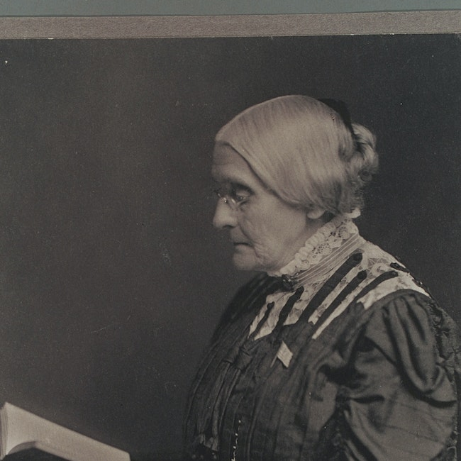 Susan B. Anthony seated, and reading a book