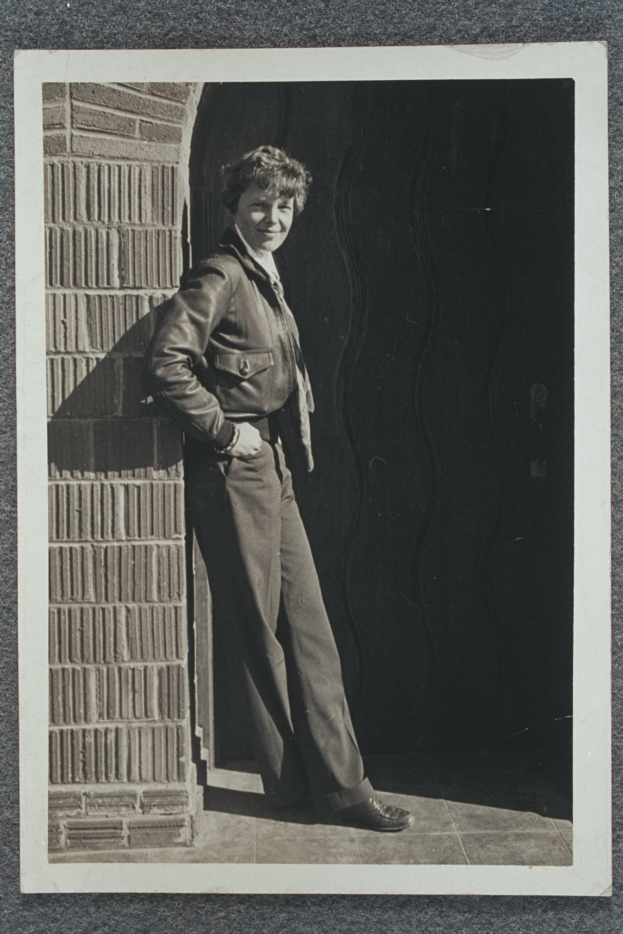 Amelia Earhart leaning against a wall