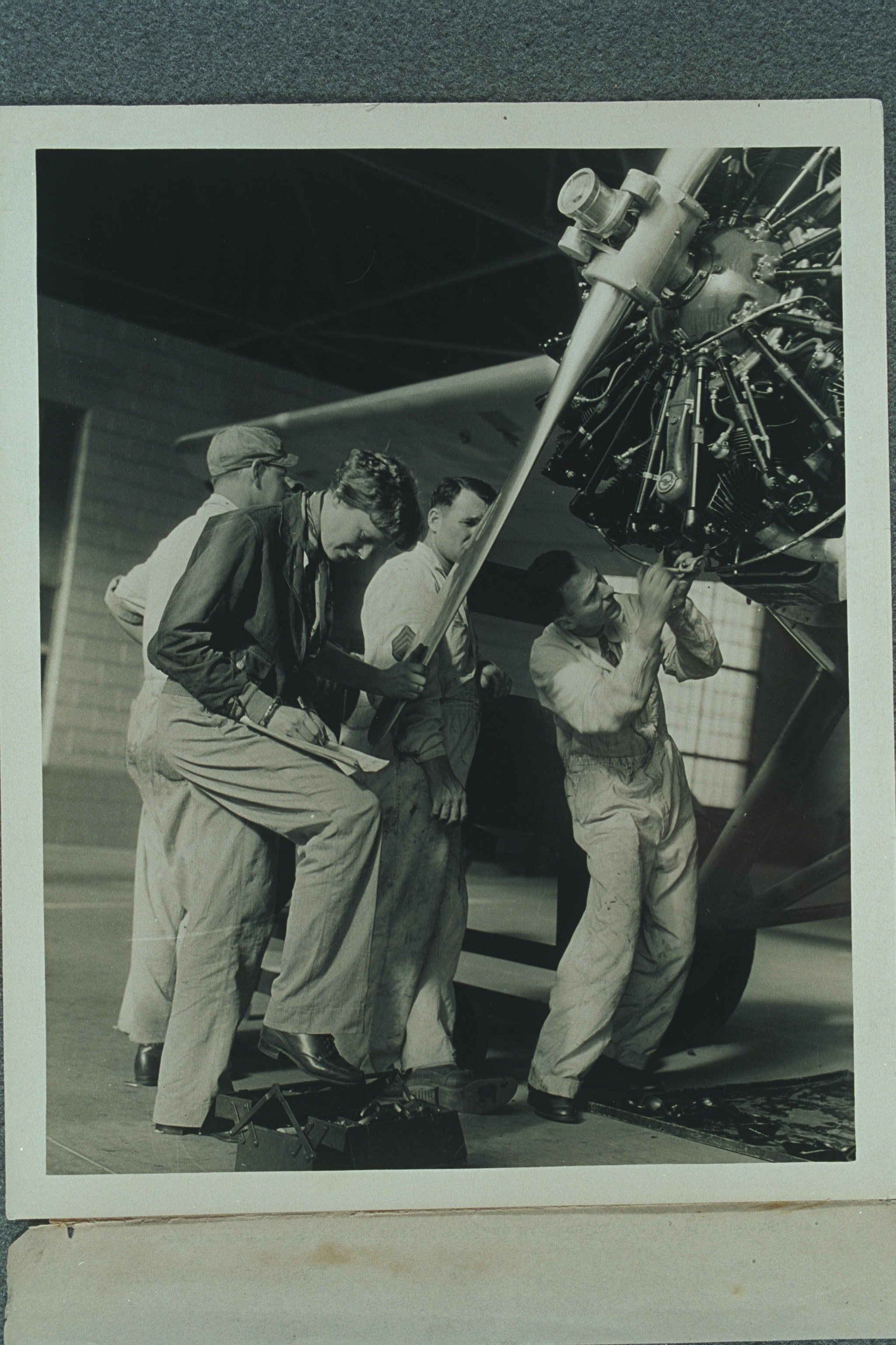 Amelia Earhart and three men checking the propellor of her airplane