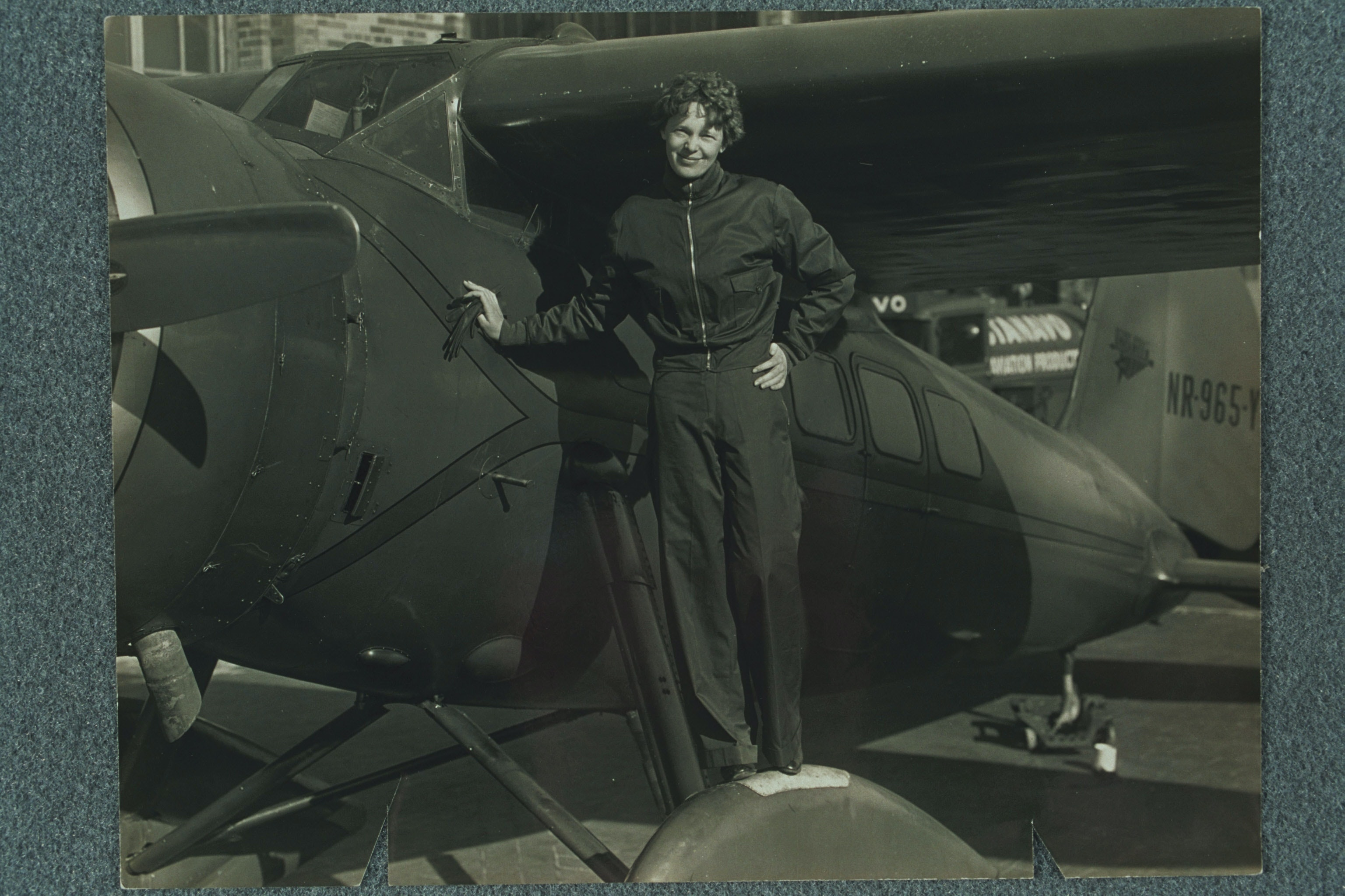 "Amelia Earhart standing on the wheel of her airplane, probably the Lockheed ""Vega."""