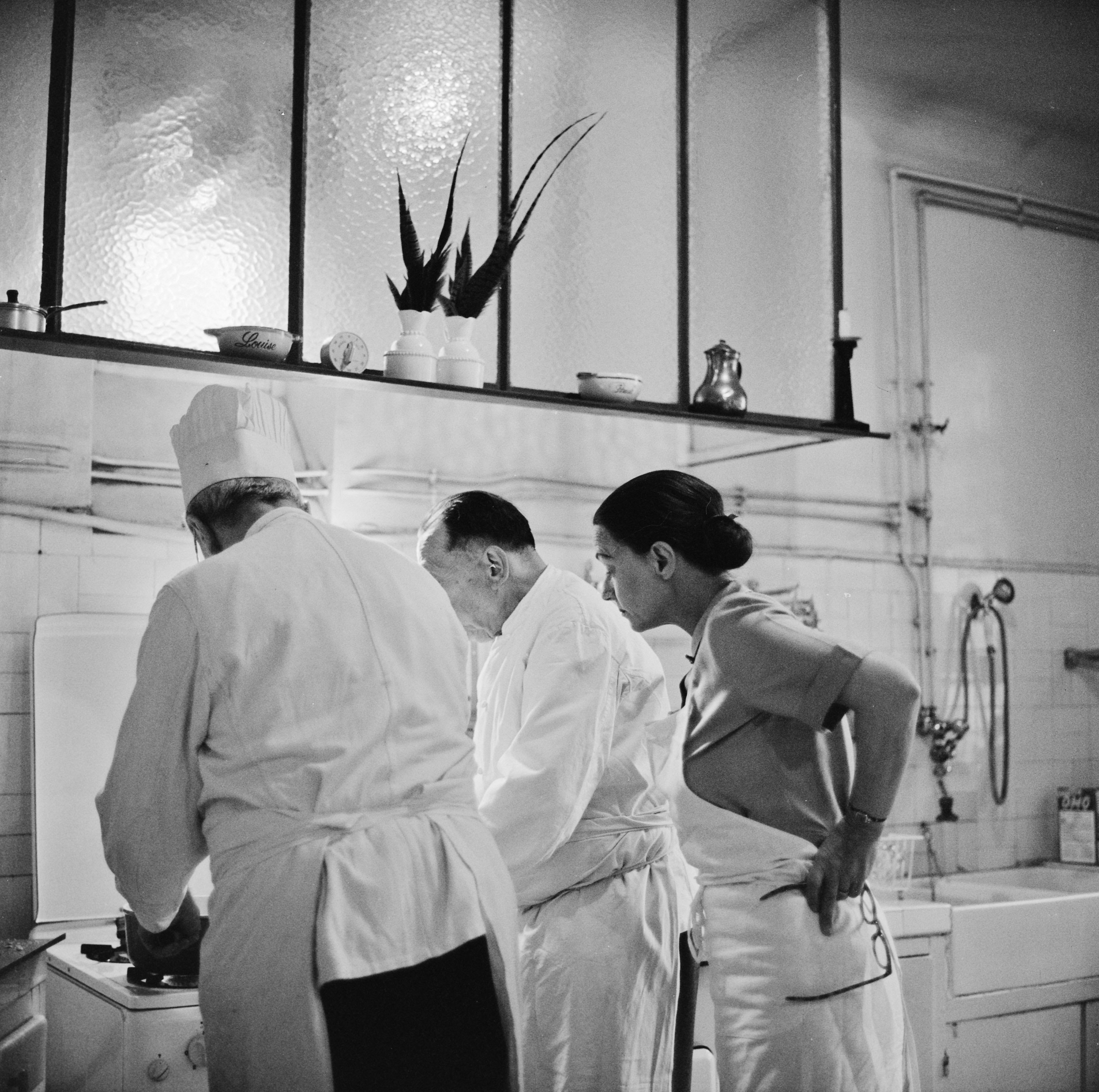 Julia Child and two others working in the kitchen
