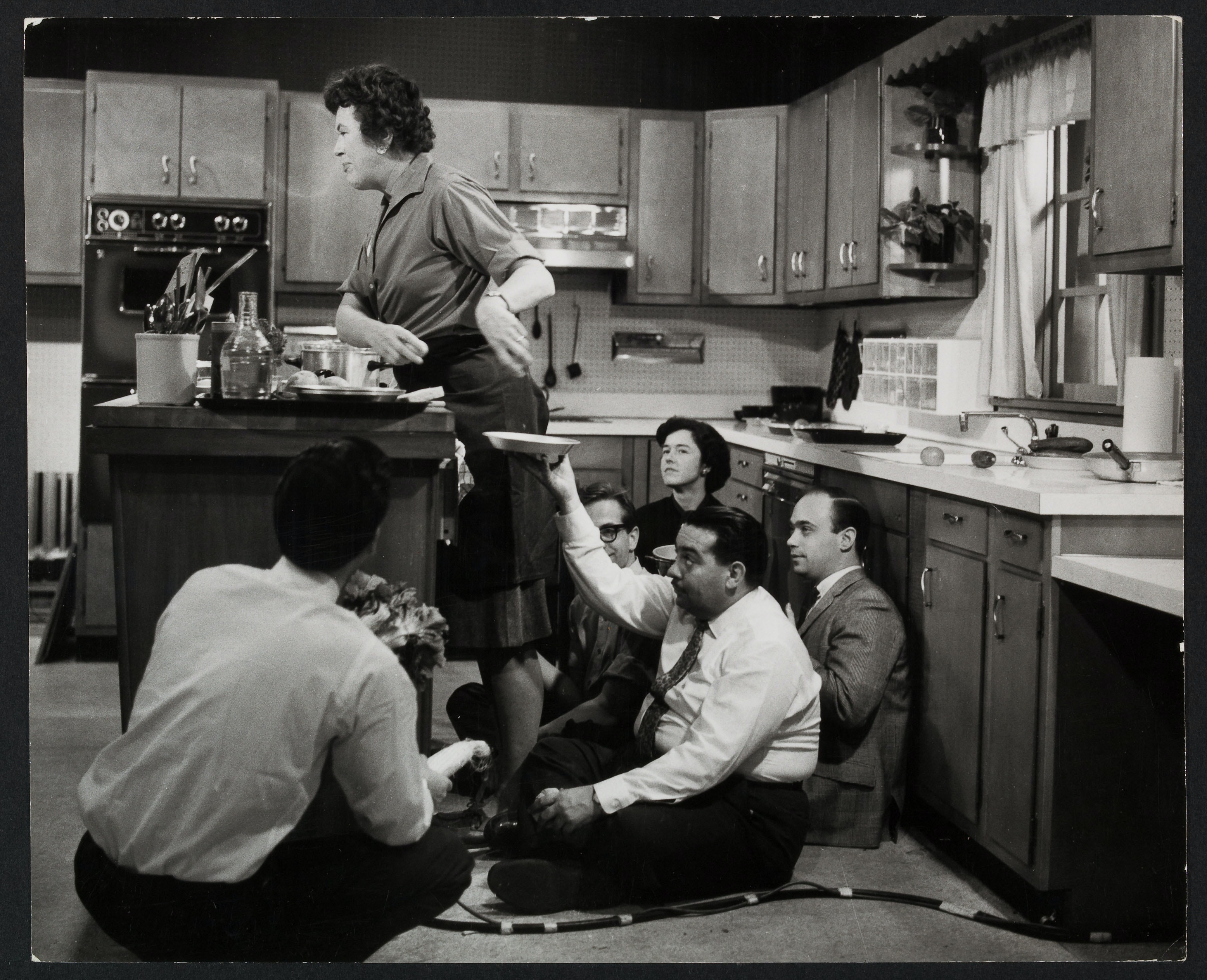 Julia Child filming a 1964 promo with four others at the Cambridge Gas and Electric Kitchen