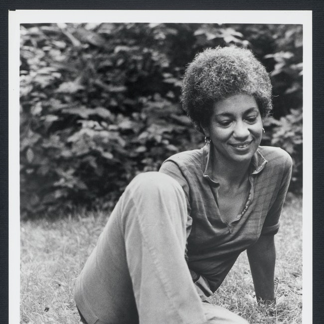 June Jordan seated outdoors in grass