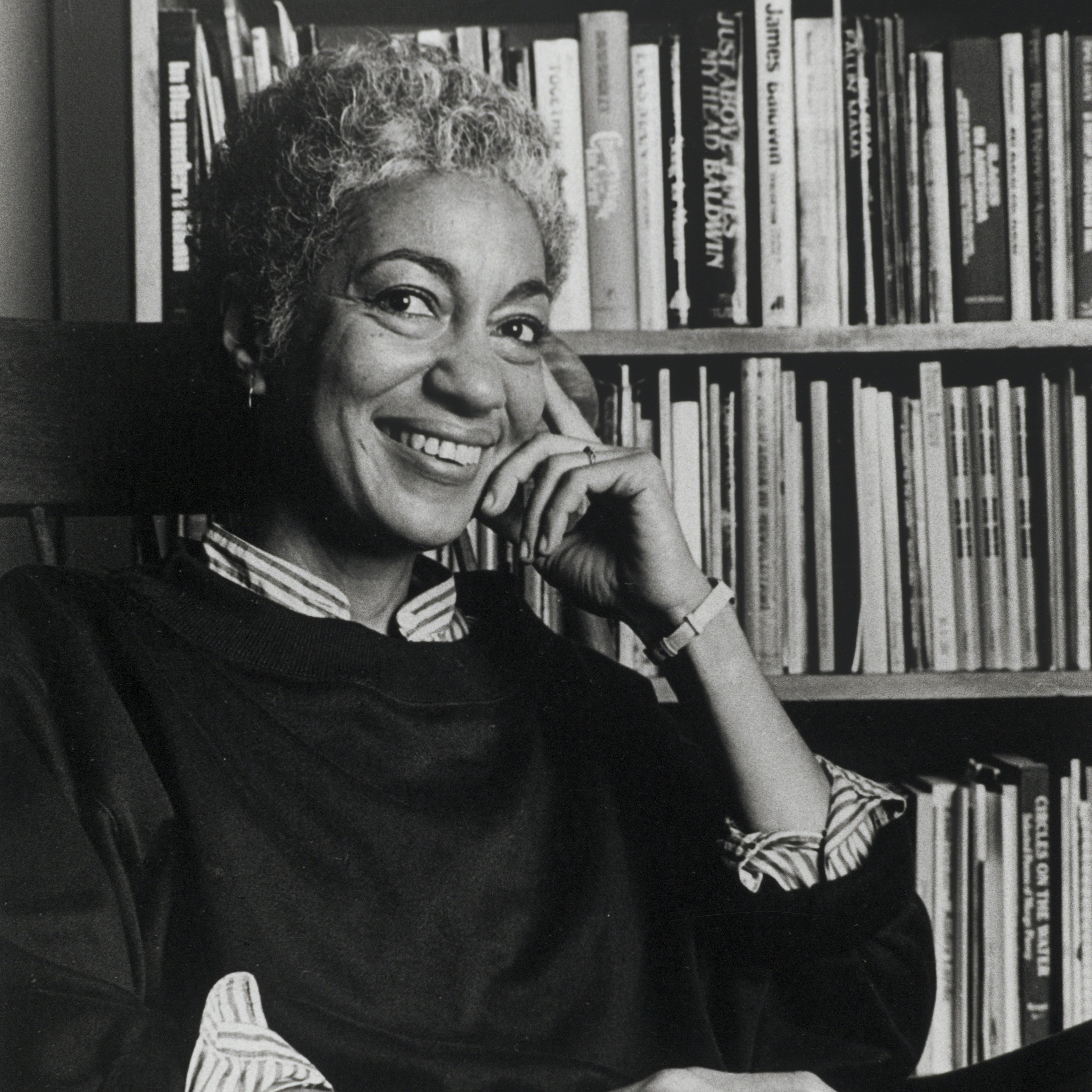 June Jordan seated in front of bookcase