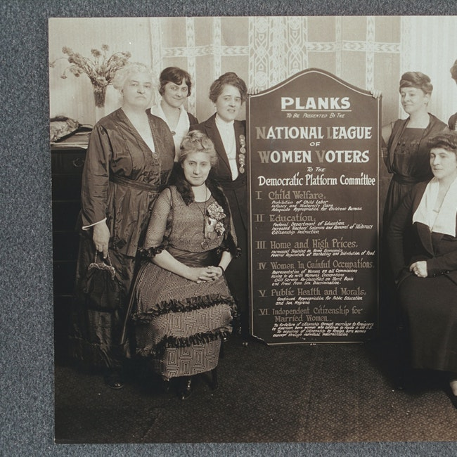 Group portrait of eight women holding a sign listing the planks to be presented by the NLWV to the Democratic Platform Committee. Pattie Ruffner Jacobs (left) and Maud Wood Park (right) are holding the sign