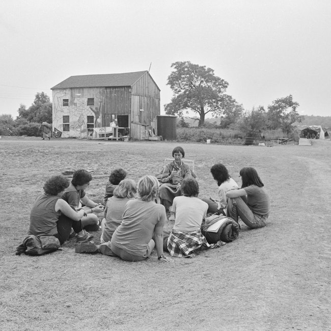 Barbara Deming with a circle of women seated on the ground
