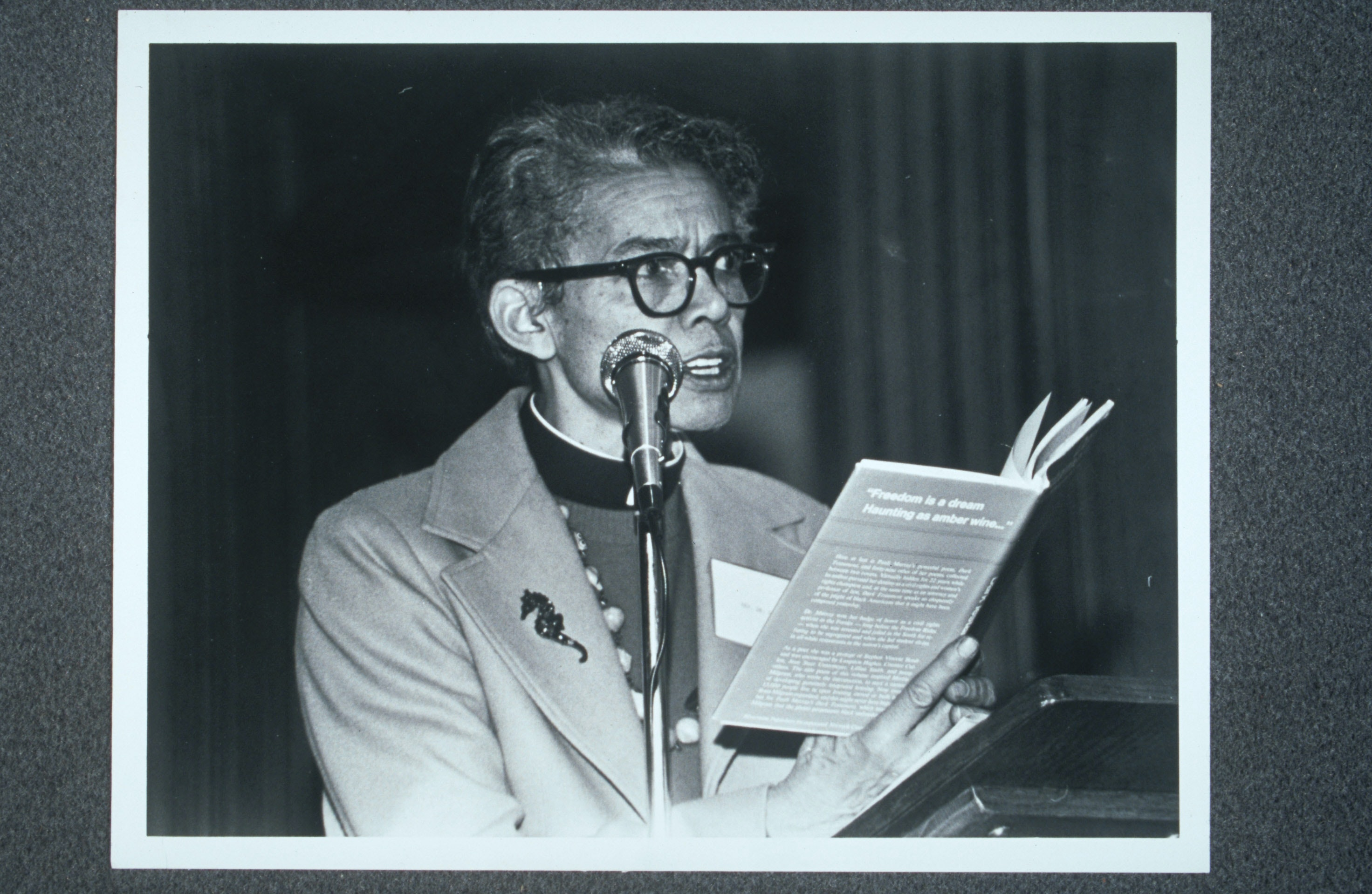 Pauli Murray standing in front of a microphone, reading from Dark Testament and Other Poems