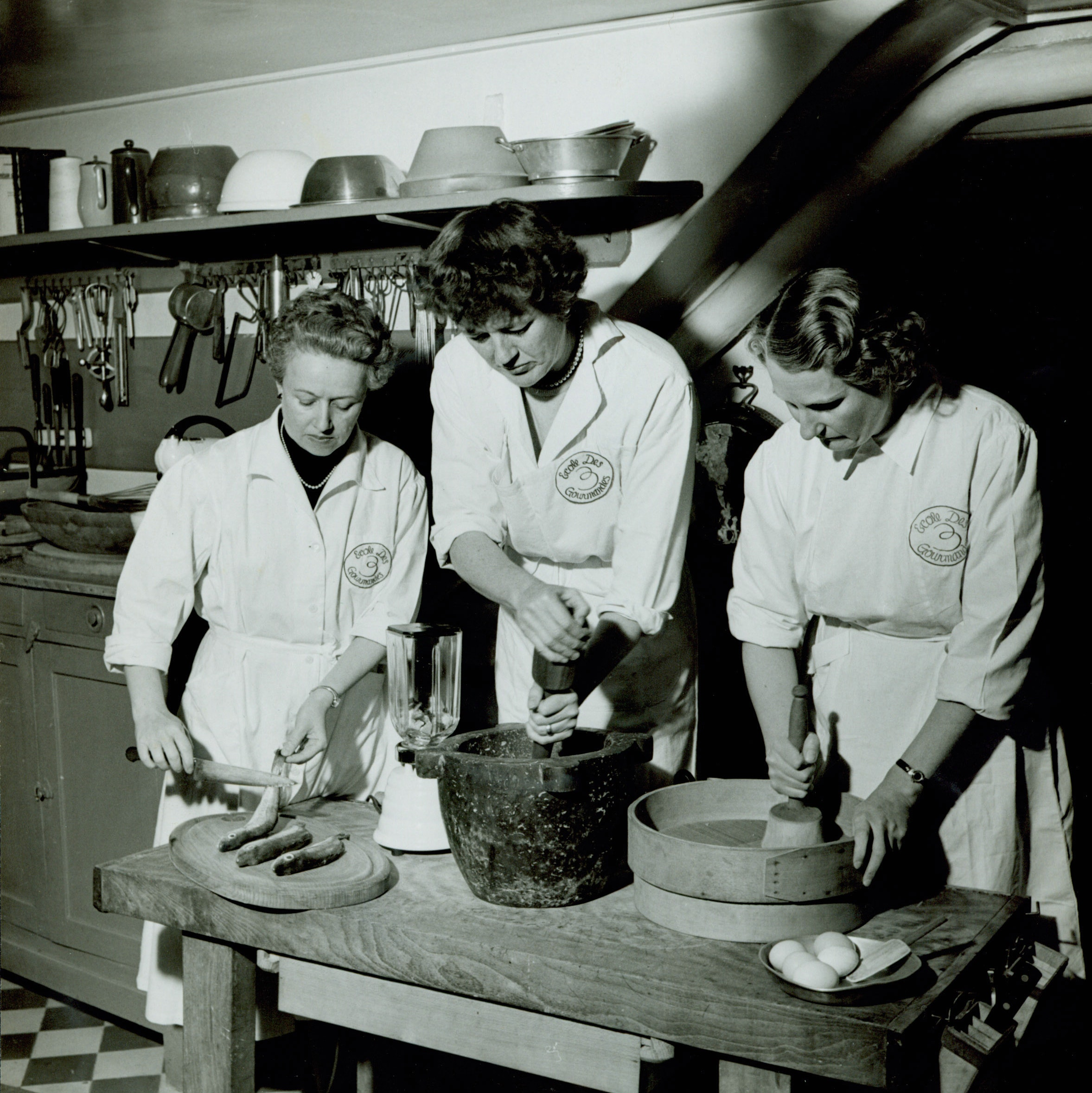 Simone Beck, Julia Child, and Louisette Bertholle cook fish at the Ecole des Trois Gourmandes