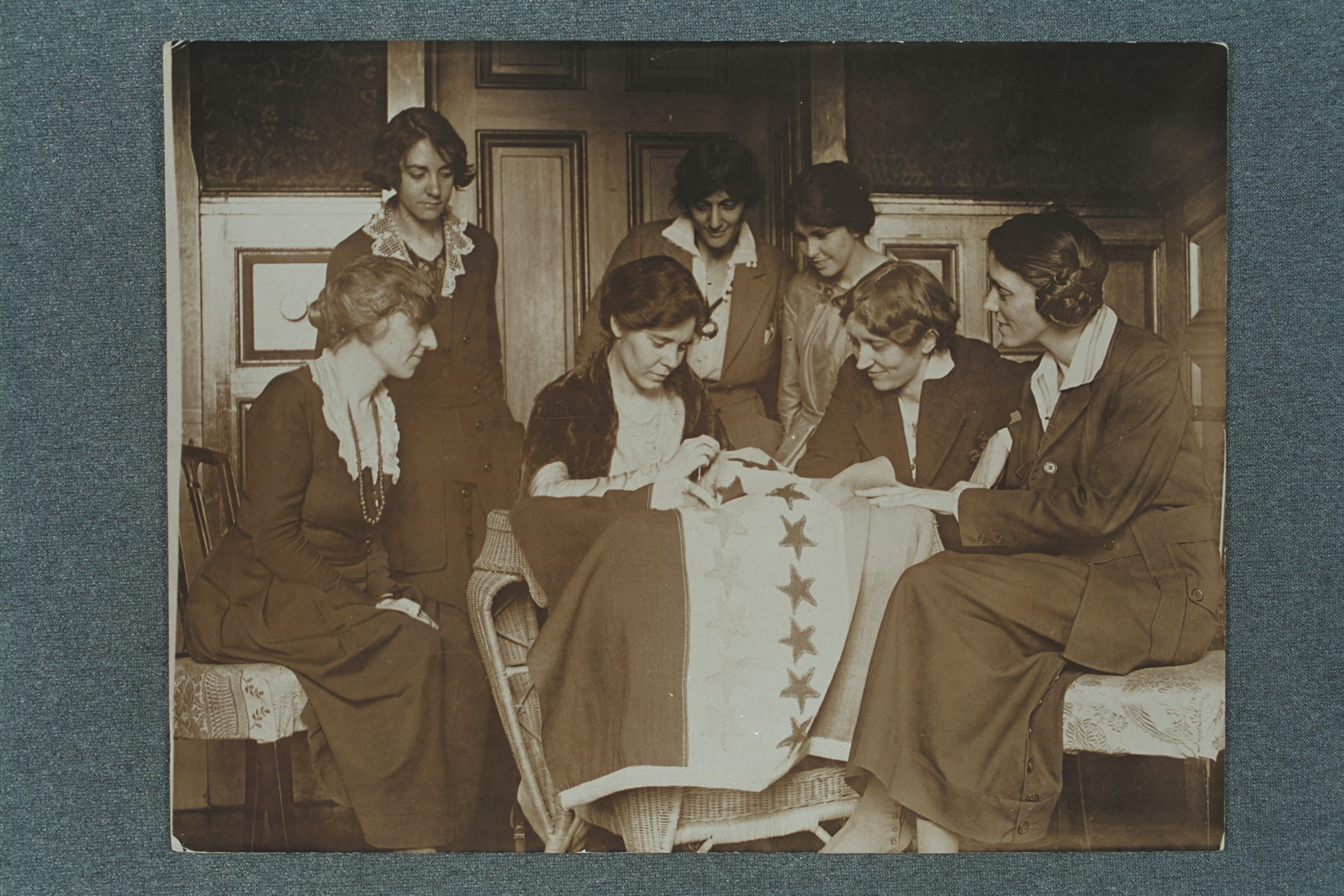 Photograph of Alice Paul sewing stars on the suffrage flag as others look on