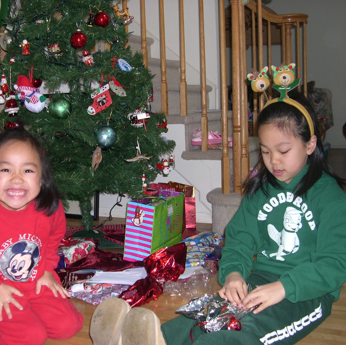 Vanessa Hu and sister sitting around Christmas tree opening gifts