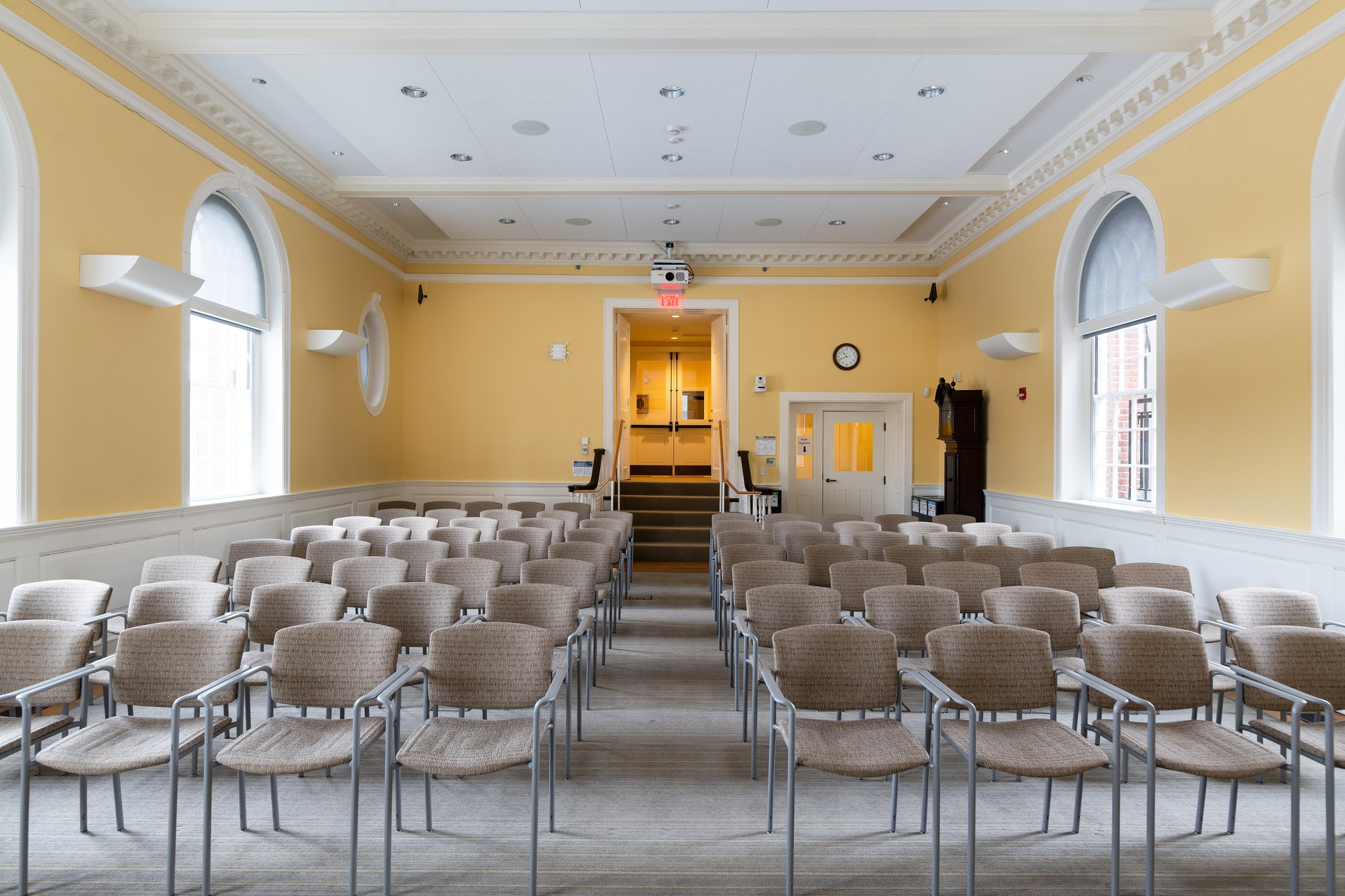 Theatre style setup for seating, view is from the front of the room. Down the middle of the seats leads to a small stairwell and entrance of the room. Walls are yellow.