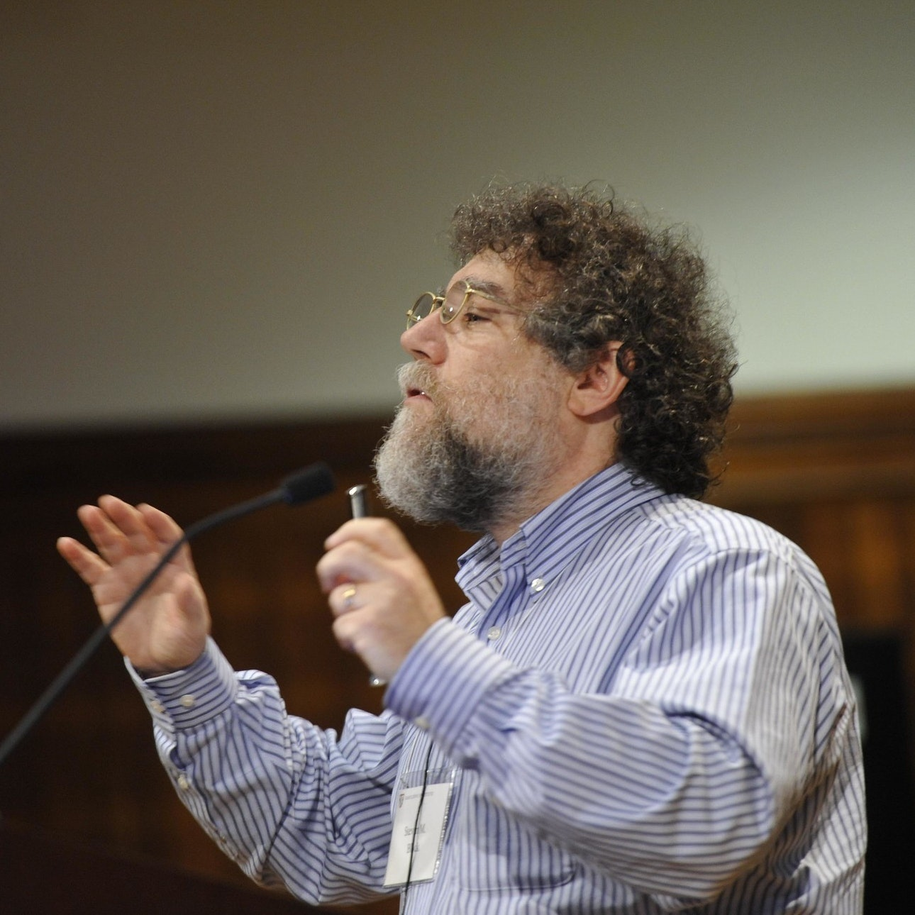 A person speaks in front of an audience at a conference.