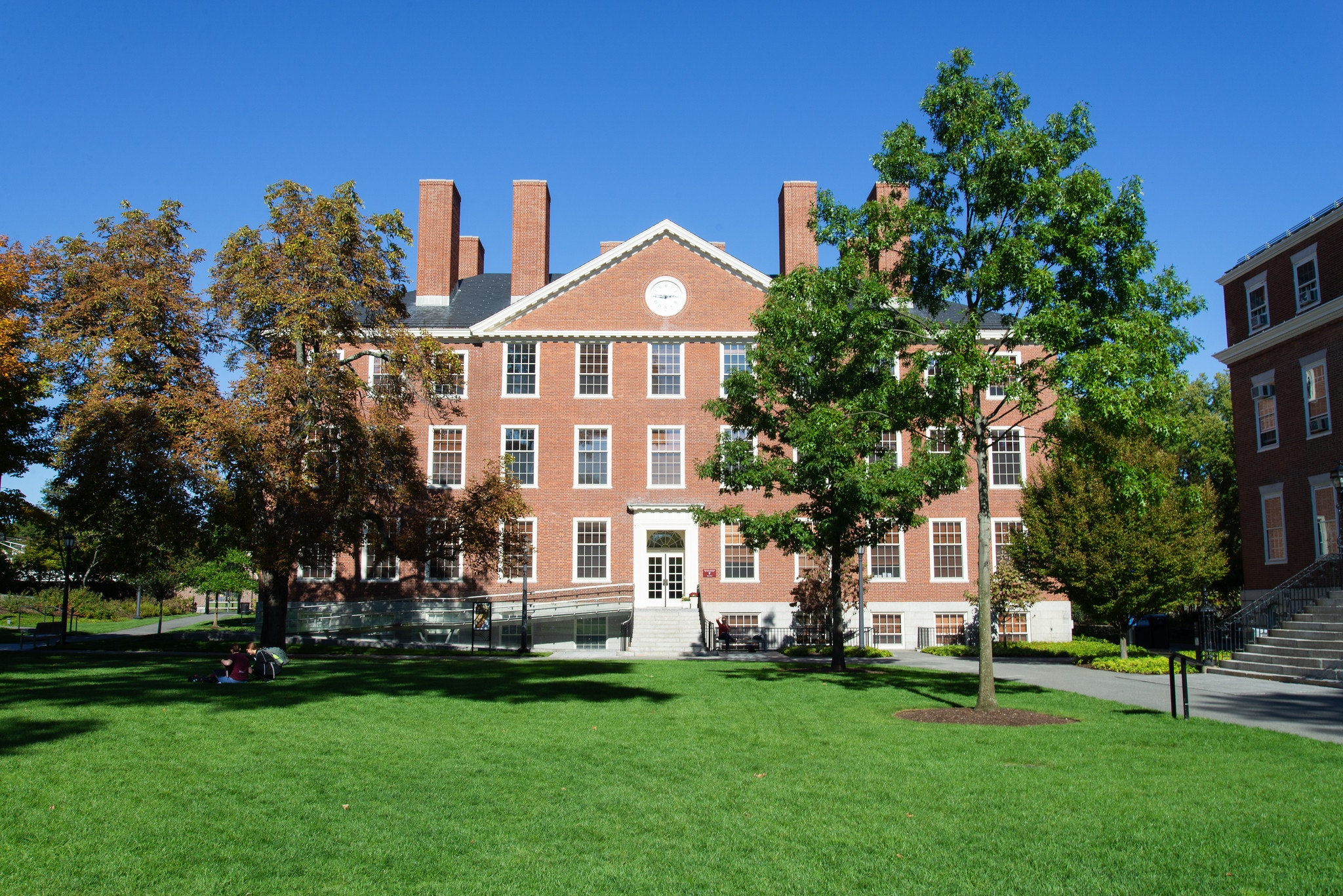 A brick office building with adjacent trees and green grass on a sunny day. The sky is blue.