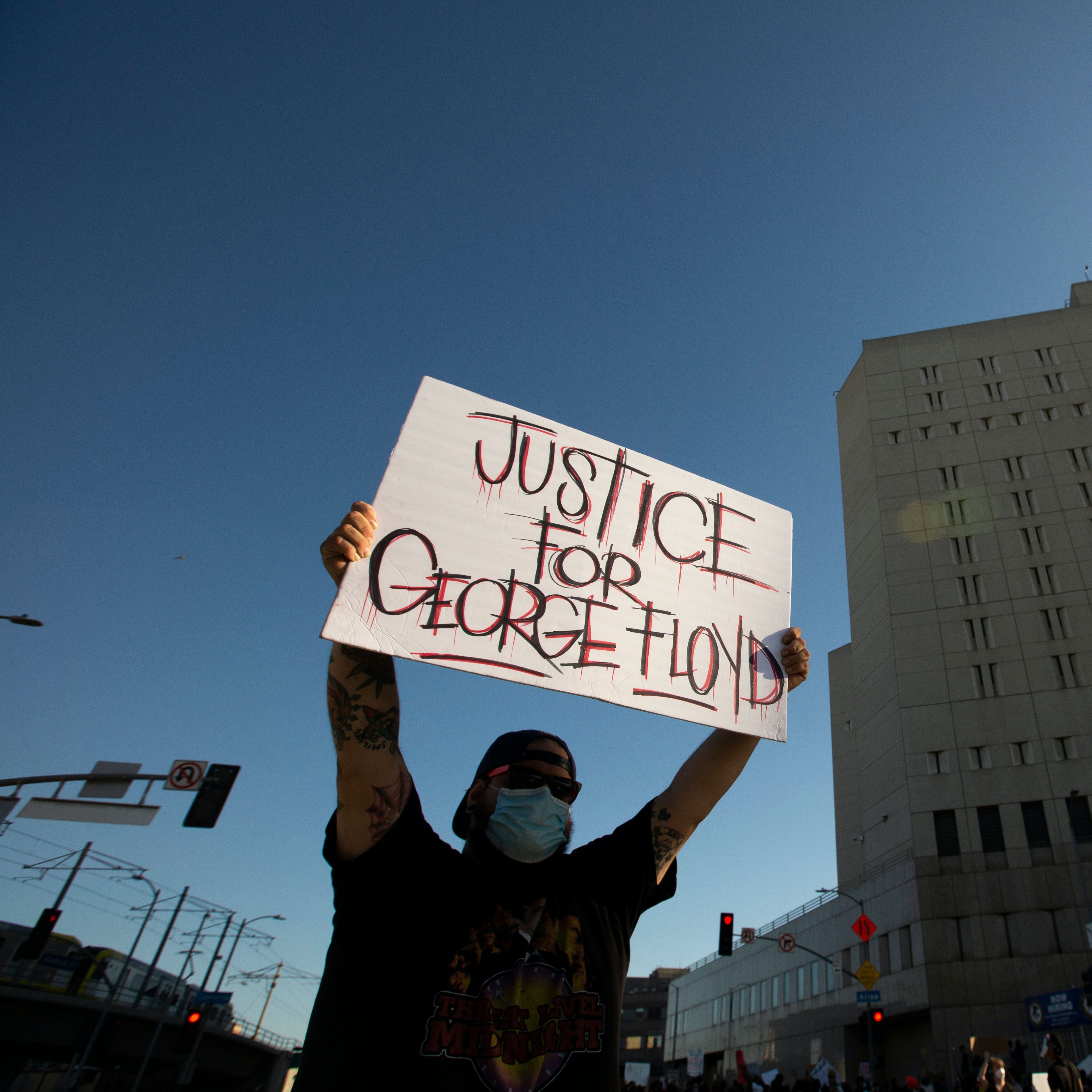 """Man holding poster that reads """"Justice for George Floyd."""" A building is in view"""