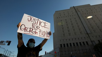 "Man holding poster that reads ""Justice for George Floyd."" A building is in view"