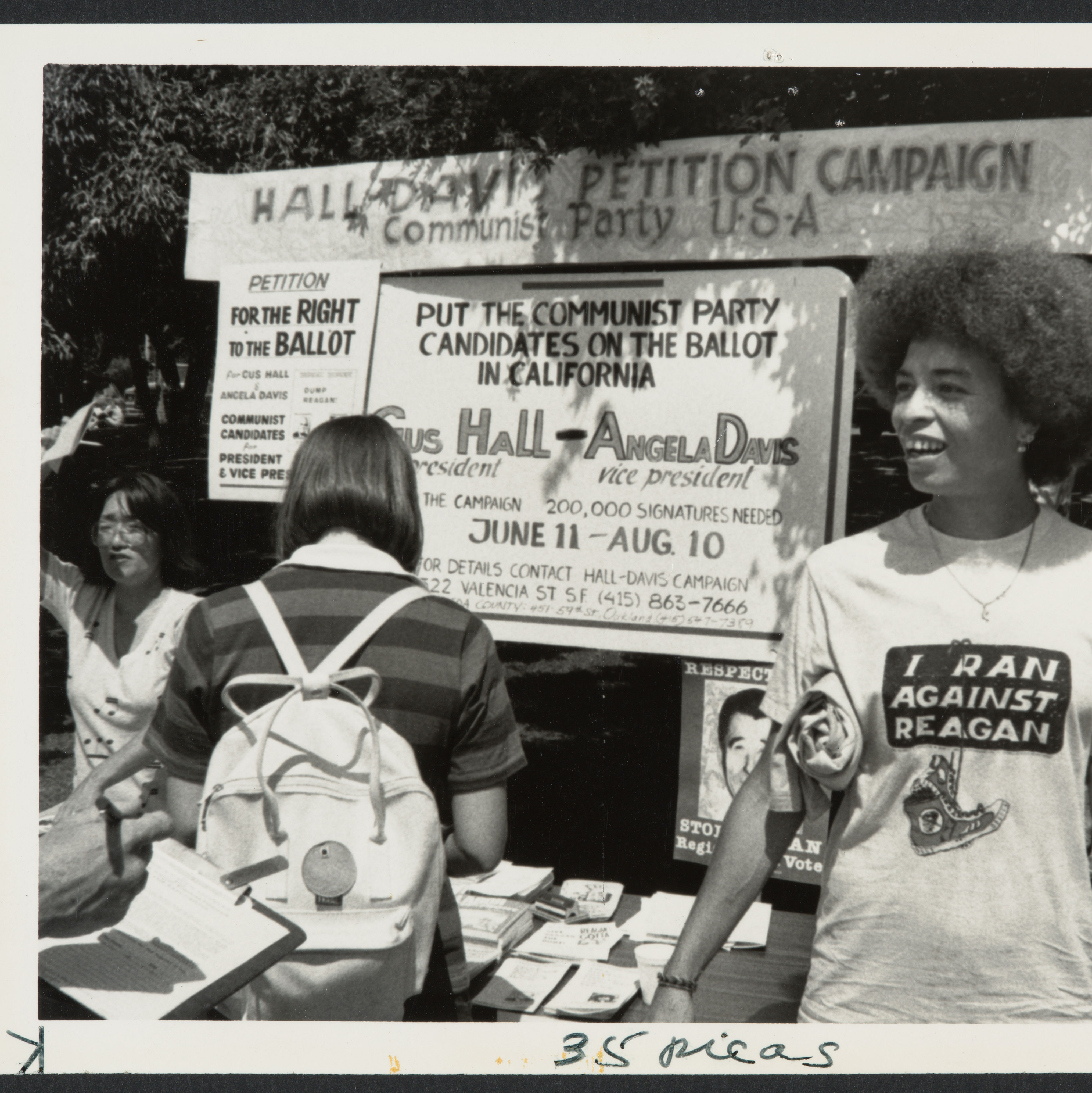 Black & white image of Angela Davis at campaign event, in front of booth.