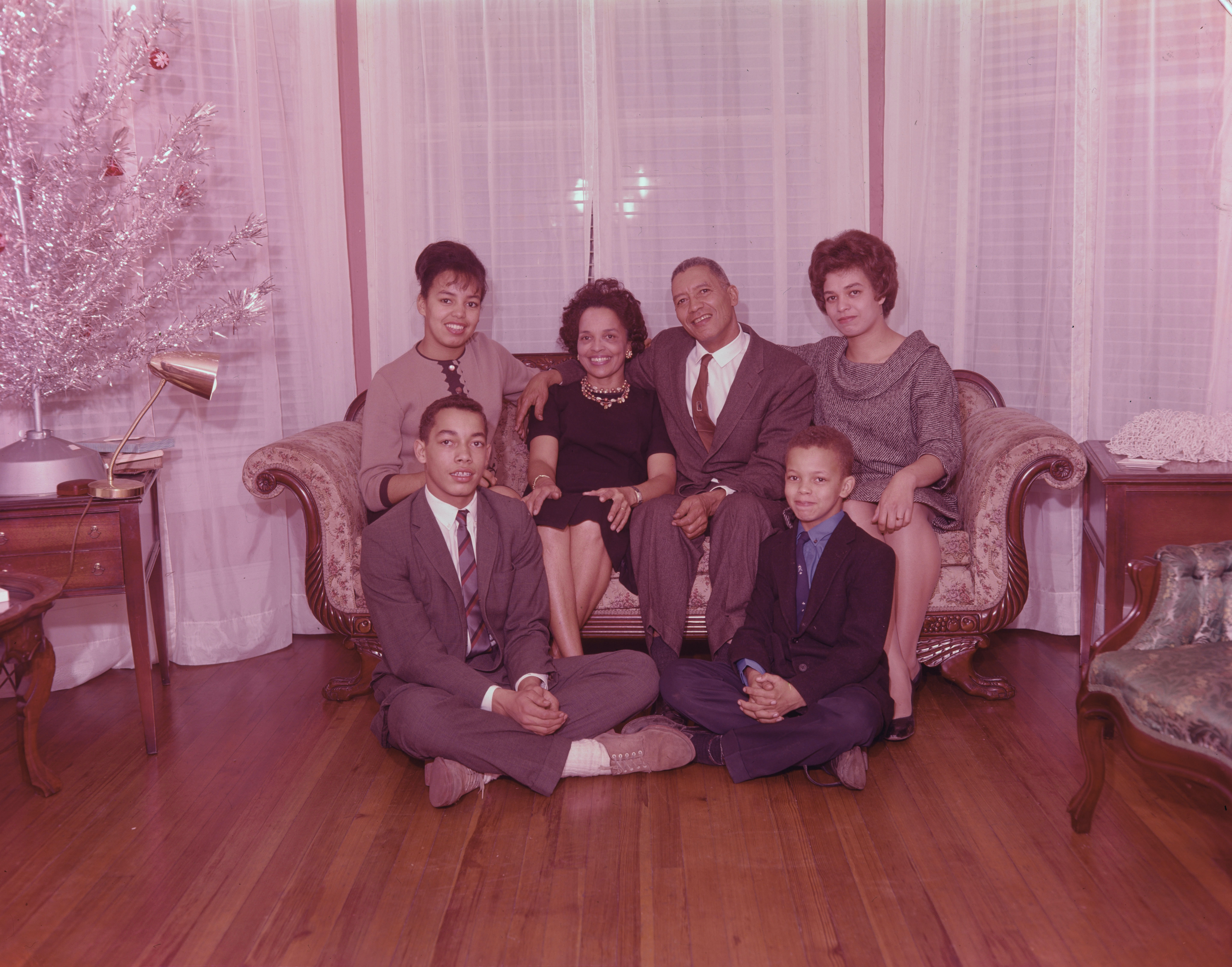 Family photo with 4 members sitting on couch, and two members sitting on the wood floor in front of the couch.