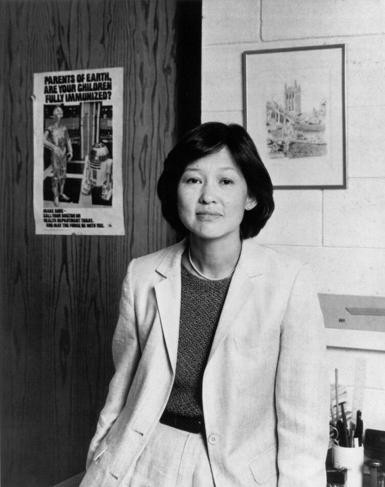 Black & White image of Alice Huang in business dress suit in what appears to be a classroom or office
