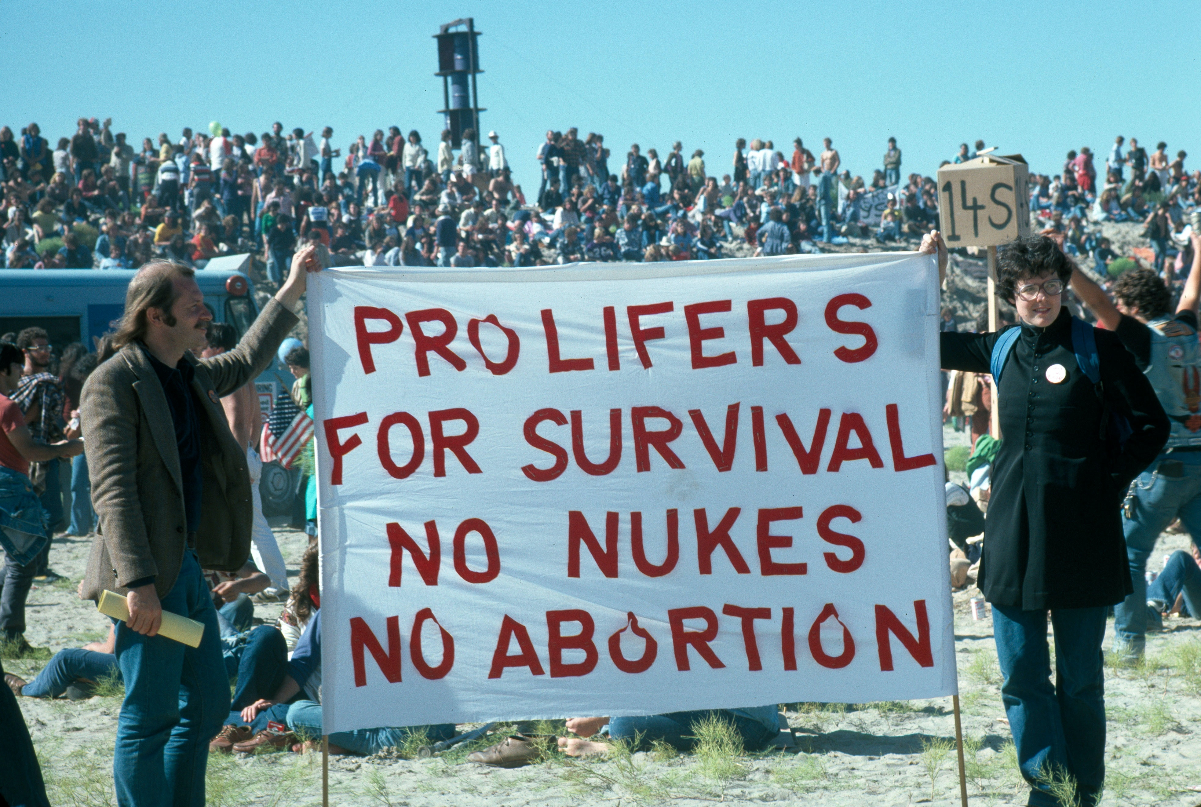 """At an outdoor demonstration, two people hold a sign that reads """"Pro Lifers For Survival No Nukes No Abortion."""""""