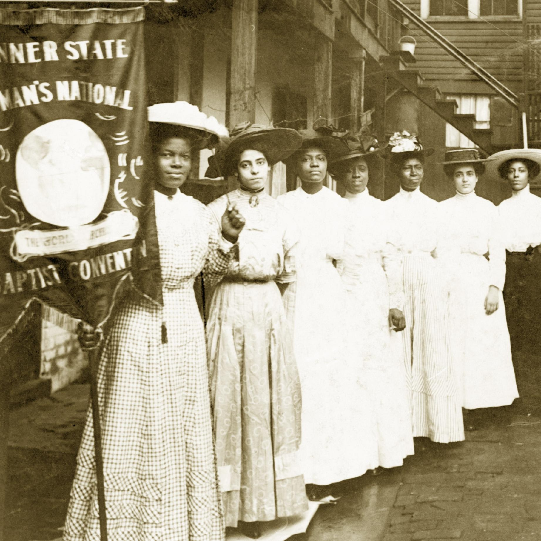 """Nine African-American women posed, standing, full length, with Nannie Burroughs holding banner reading, """"Banner State Woman's National Baptist Convention"""""""