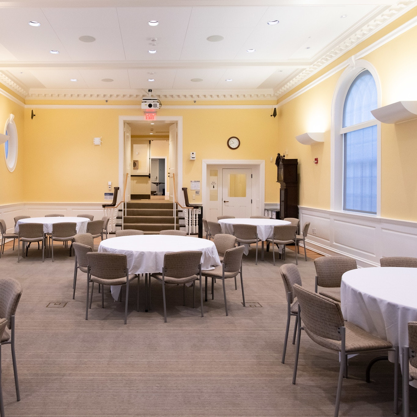 Banquet hall with five circular tables dressed in white table-cloth. Each table seats 8 people. View is from the front of the room, with the entrance in the back of the room. Walls are yellow.
