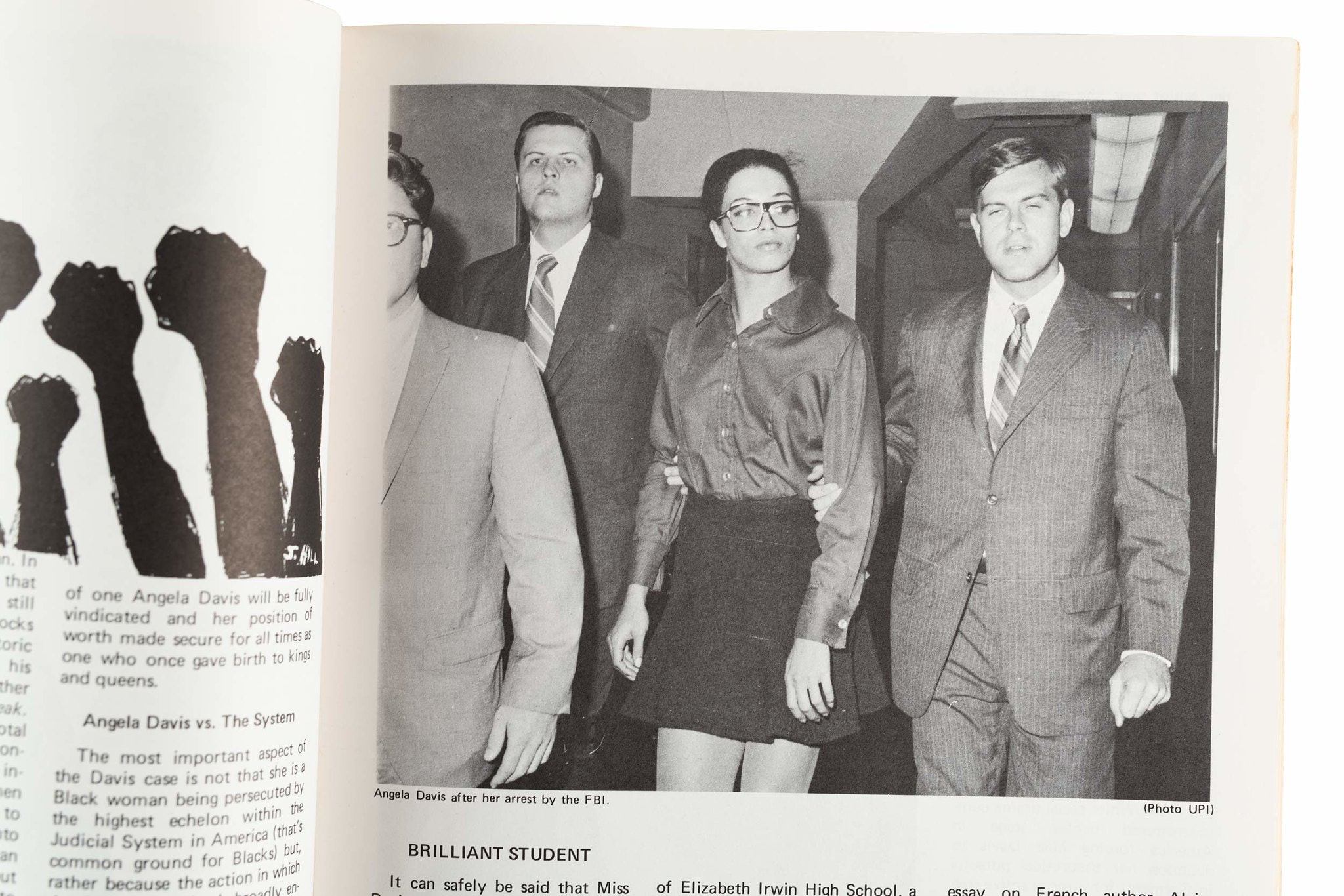 Angela Davis in between two men, each grabbing one of her arms.