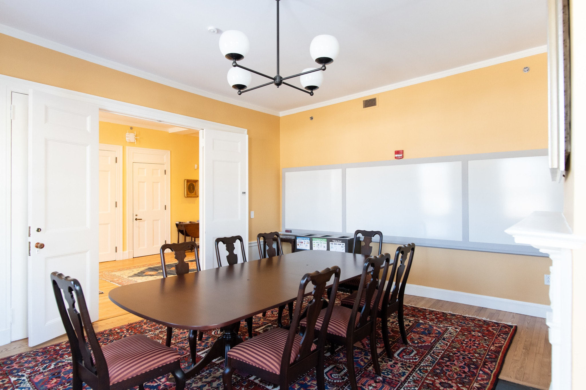 Another angle of dark brown wood conference table with 8 seats lined around. Entrance is in view, with two white doors open, and 3 white boards mounted to the wall behind the table. Walls are yellow.