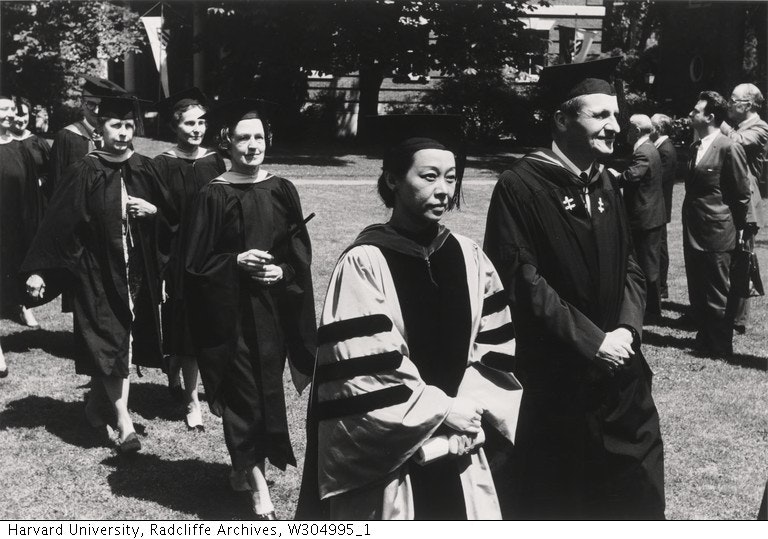 Professor Rulan Chao Pian walking in graduation cap and gown