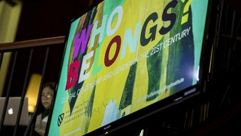 """A screen that reads, """"Who Belongs? Global Citizenship and Gender in the 21st Century."""""""