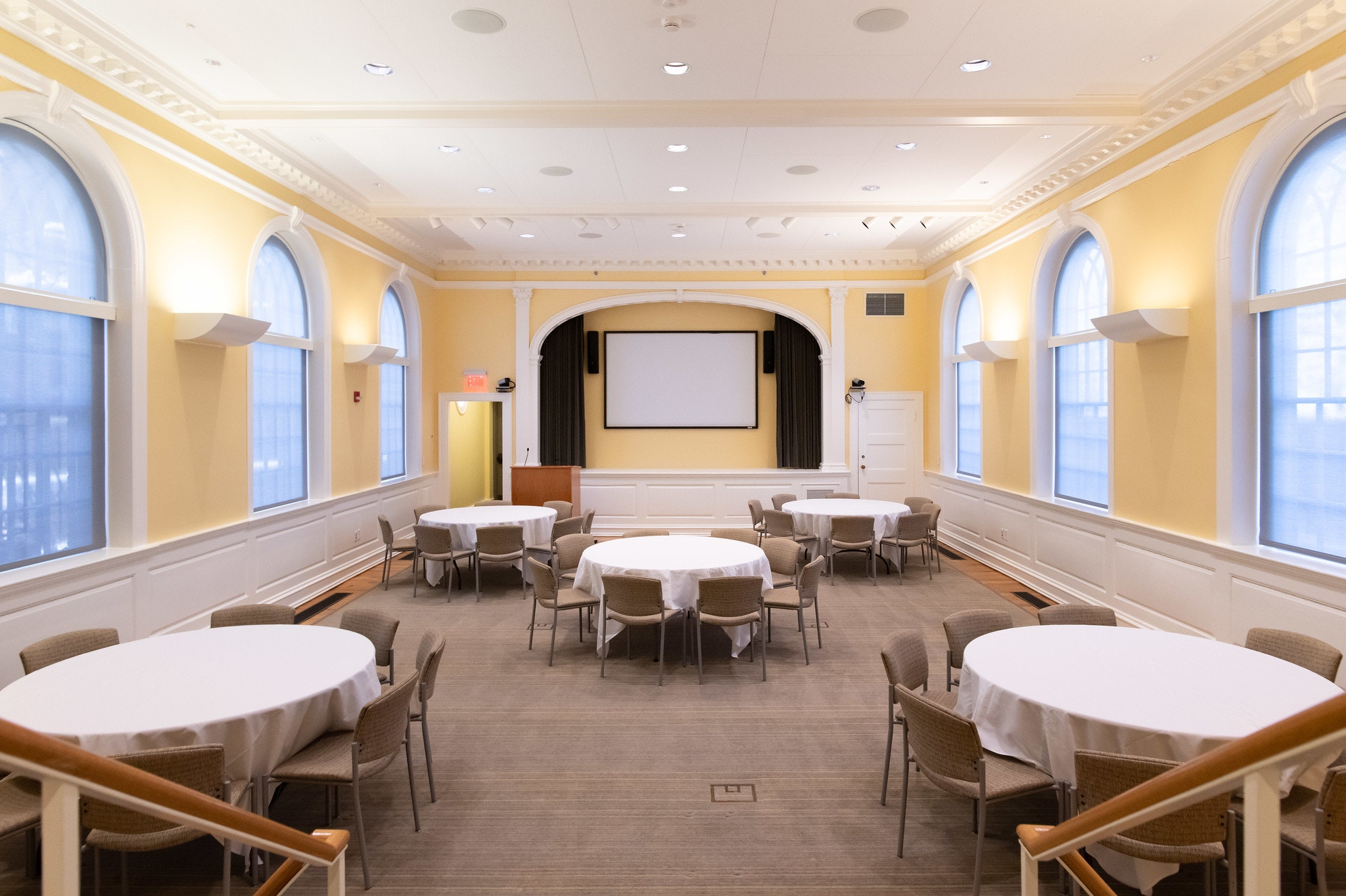 Banquet hall with five circular tables dressed in white table-cloth. Each table seats 8 people. White projector screen is mounted to the wall at the front of the room. View is from the entrance. Walls are yellow.