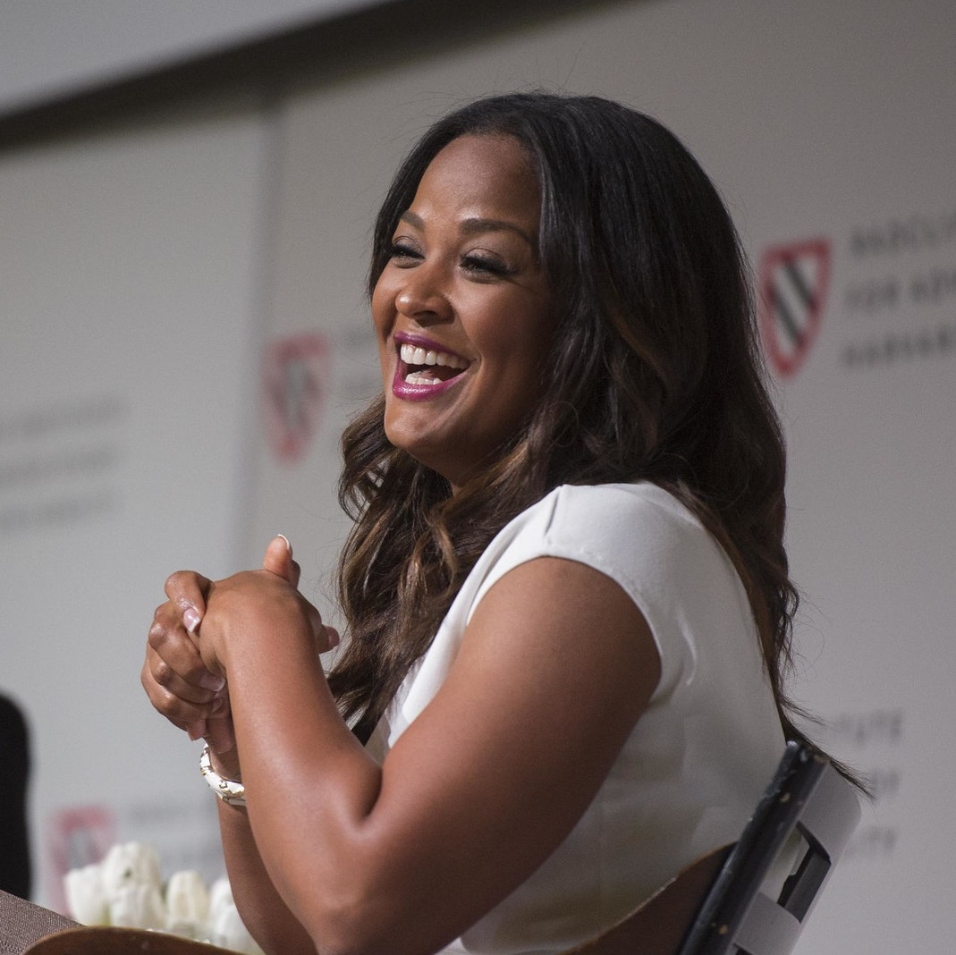 Christine Brennan and Laila Ali sit on stage in conversation. Ali turns towards the audience and smiles.