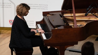 A woman plays piano on stage.